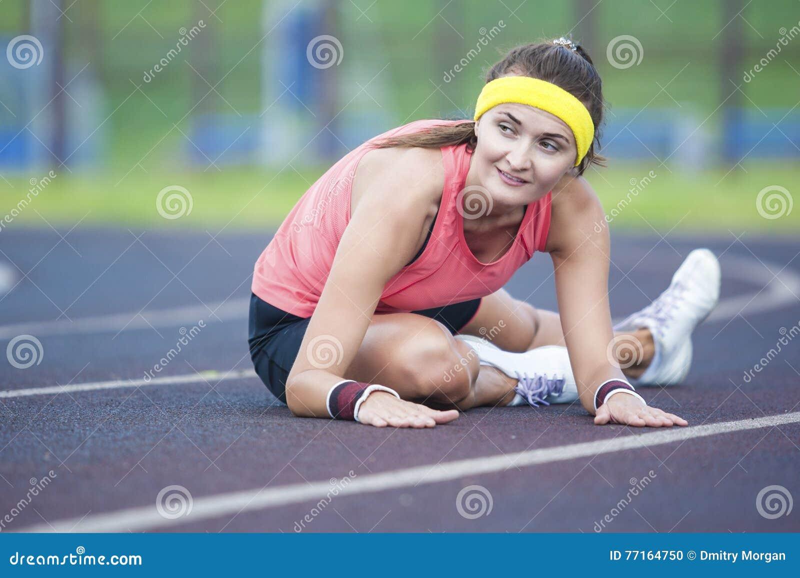 Caucasian brunettkvinnlig i idrotts- Sportgear som har ben som utomhus sträcker Excercises