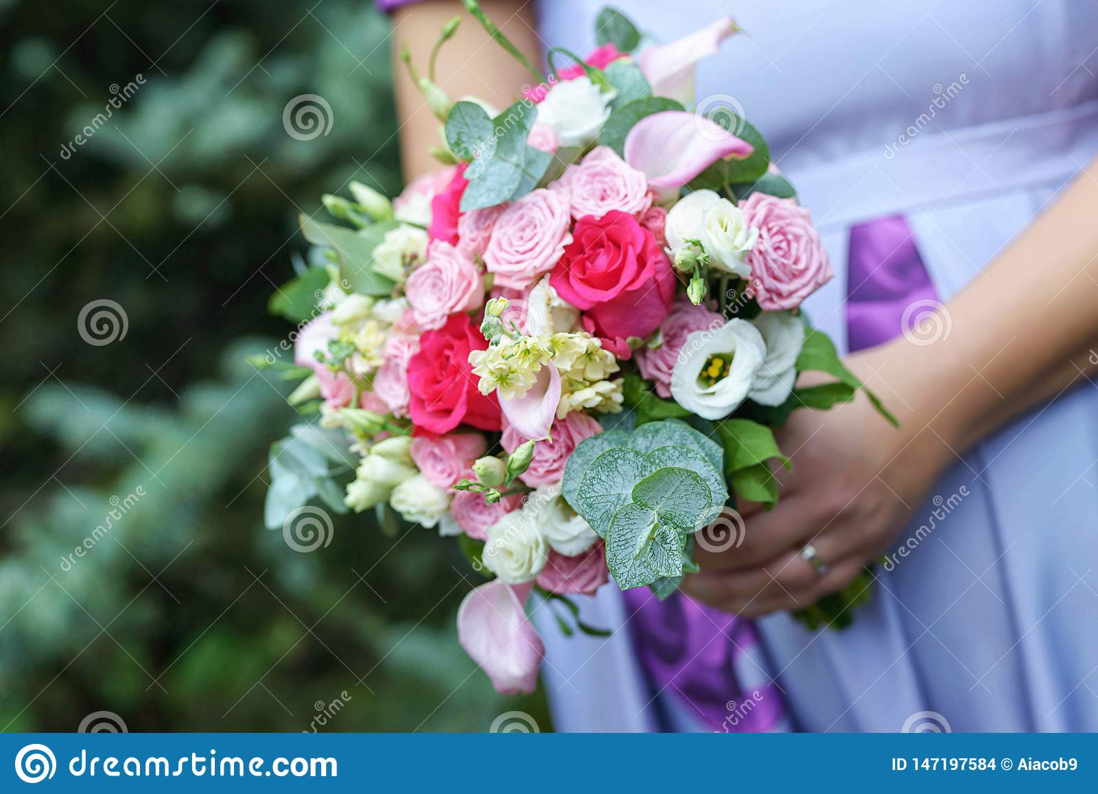 Caucasian female guest or bridesmaid wearing a lilac summer dress which shows a lovely baby bump and holding a wedding bouquet