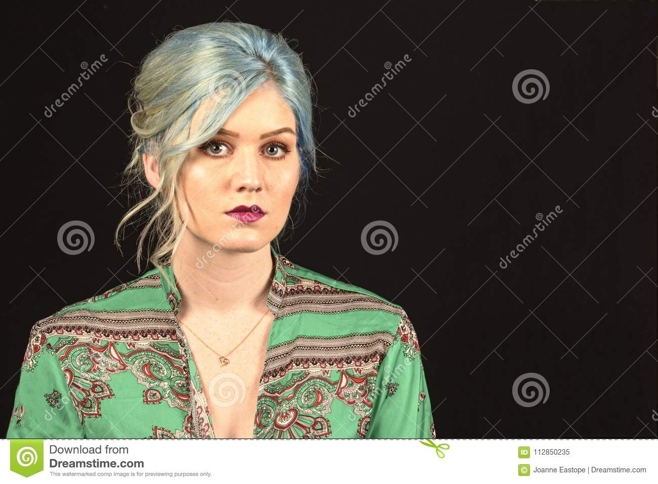 Caucasian female model, Age 22, Blue dyed hair, Red lips, green and red shirt. Isolated on black background. Upper torso. Belly ex