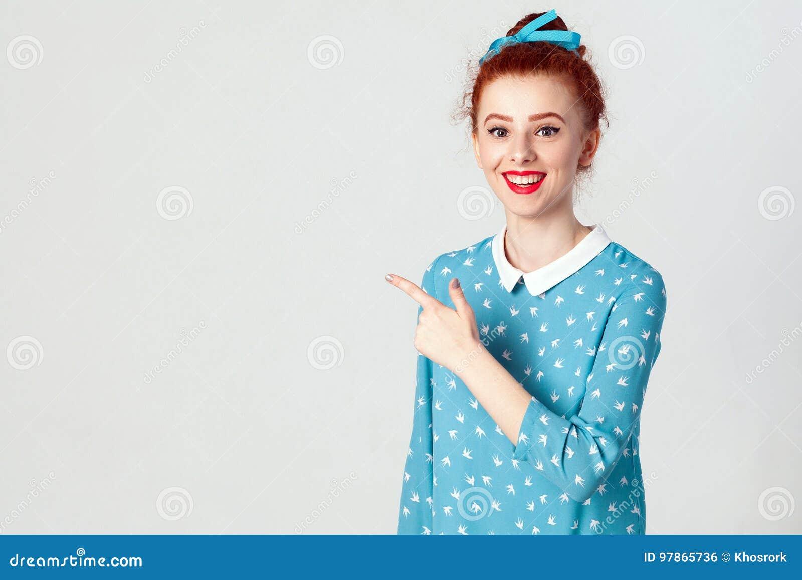 Caucasian flicka för ung rödhårig man med hårbullen som bort pekar hennes pekfinger och att indikera kopieringsutrymme på den vit