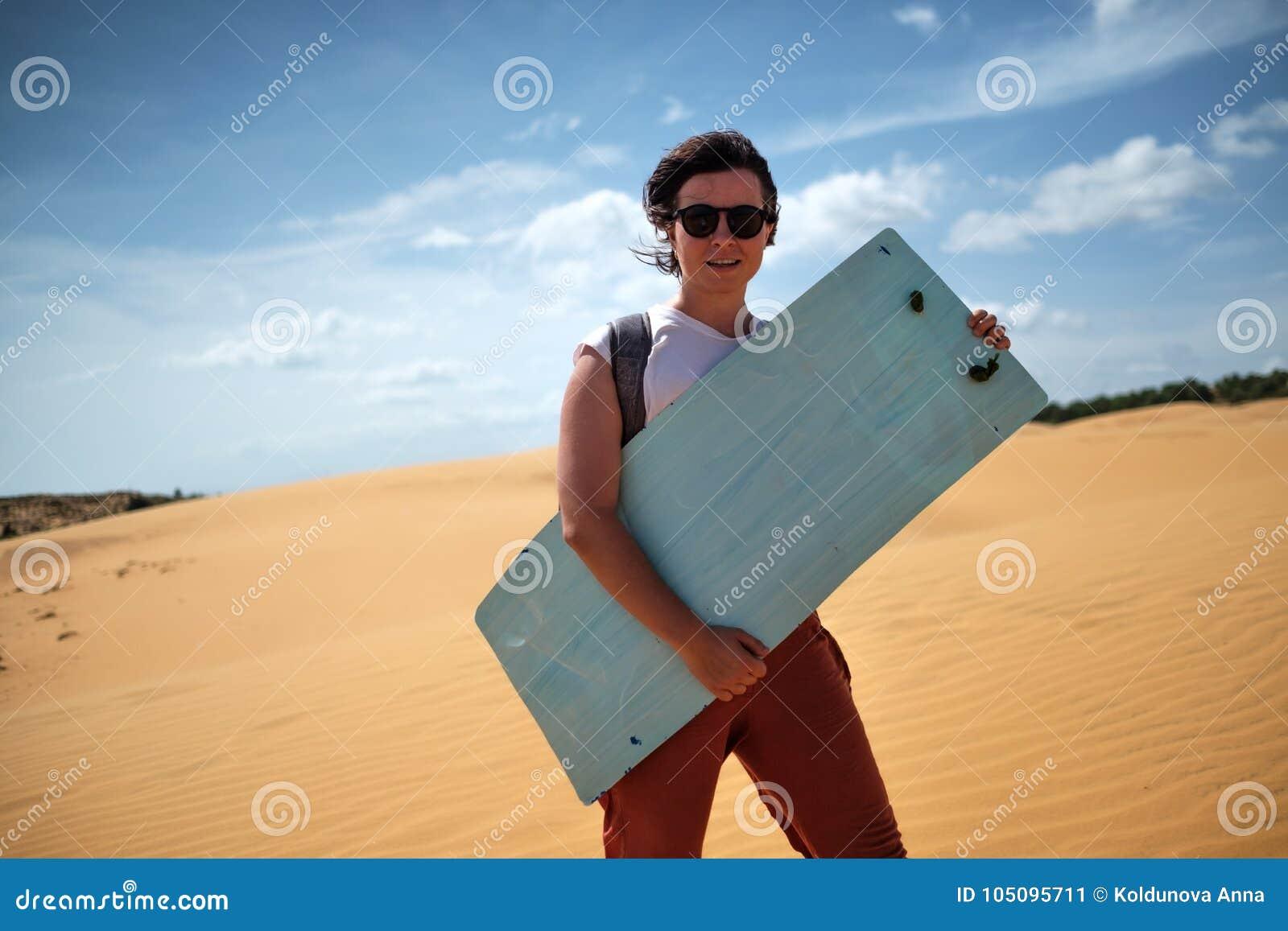 Caucasian flicka i solglasögon som är klar att gå sandsurfing Hon rymmer bränning i henne händer och leendet