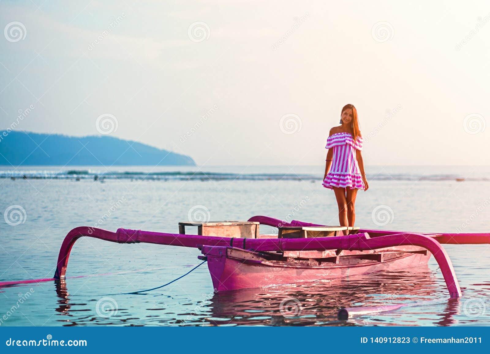 Caucasian flicka som poserar anseende på ett rosa fartyg i havet på solnedgången på ön av Gili