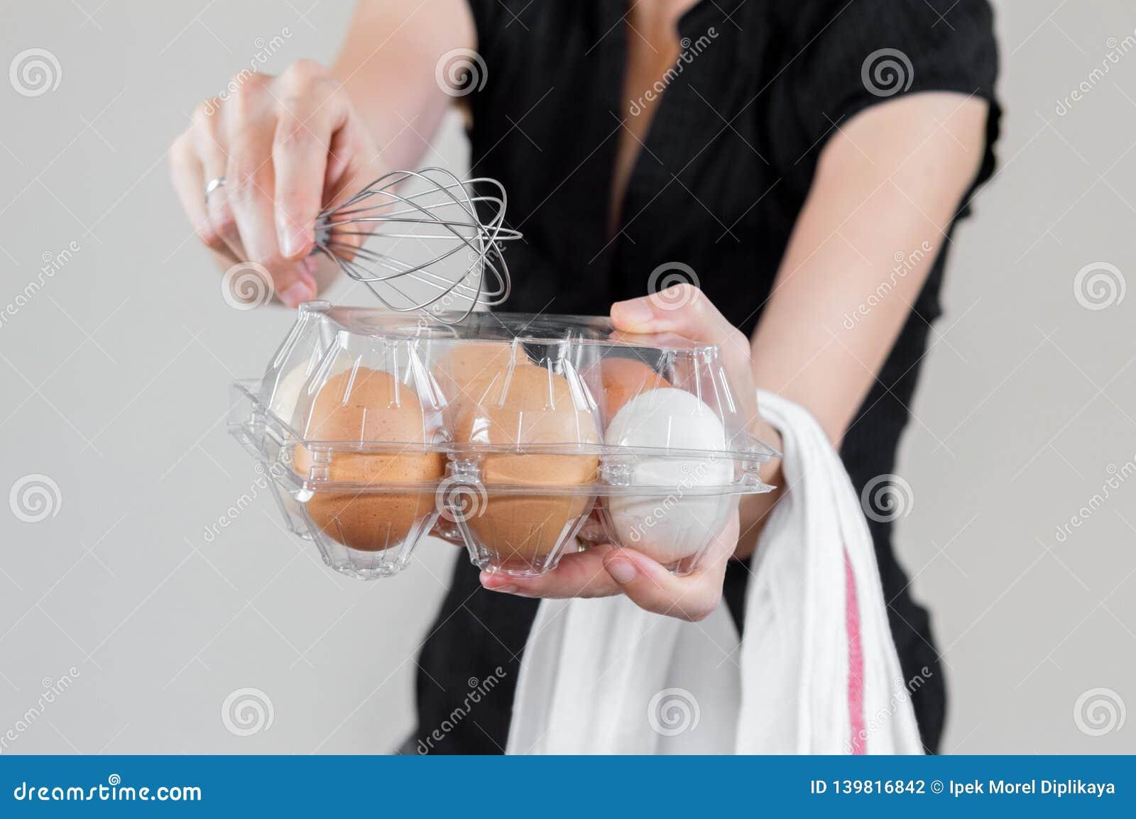 Caucasian kvinna med den svarta skjortan som mycket rymmer en eggbeater och en plast- äggask av fega ägg