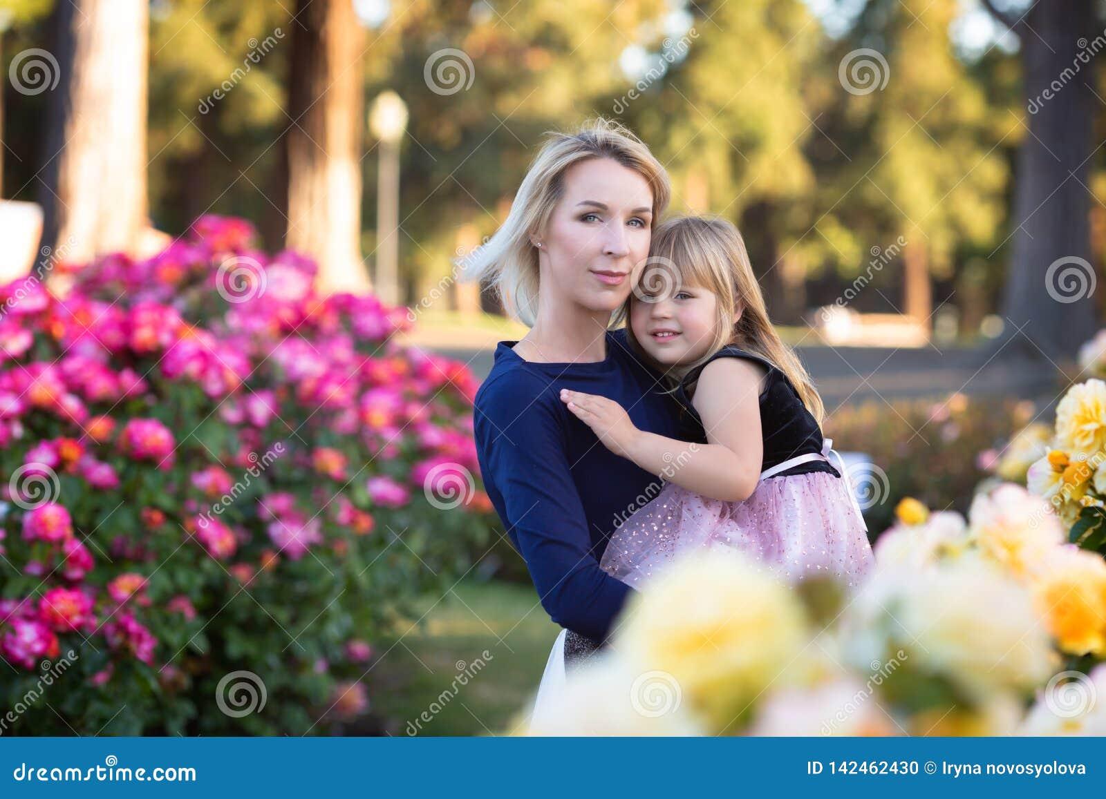 Caucasian kvinna med lilla flickan i händer i rosa trädgård, mamma och mig begrepp, kel som ser till kameran