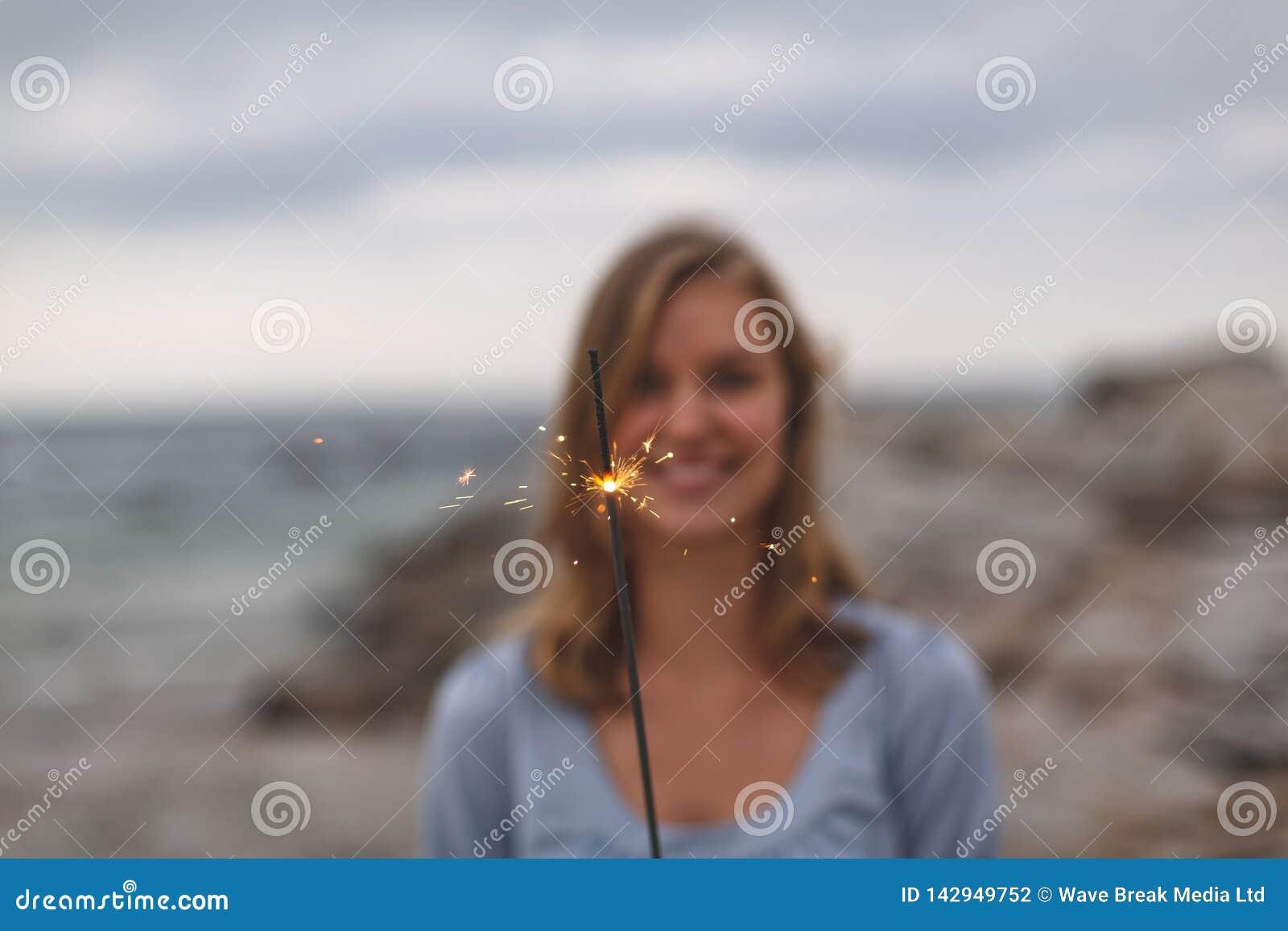 Caucasian kvinnaanseende med gnistrandet på stranden