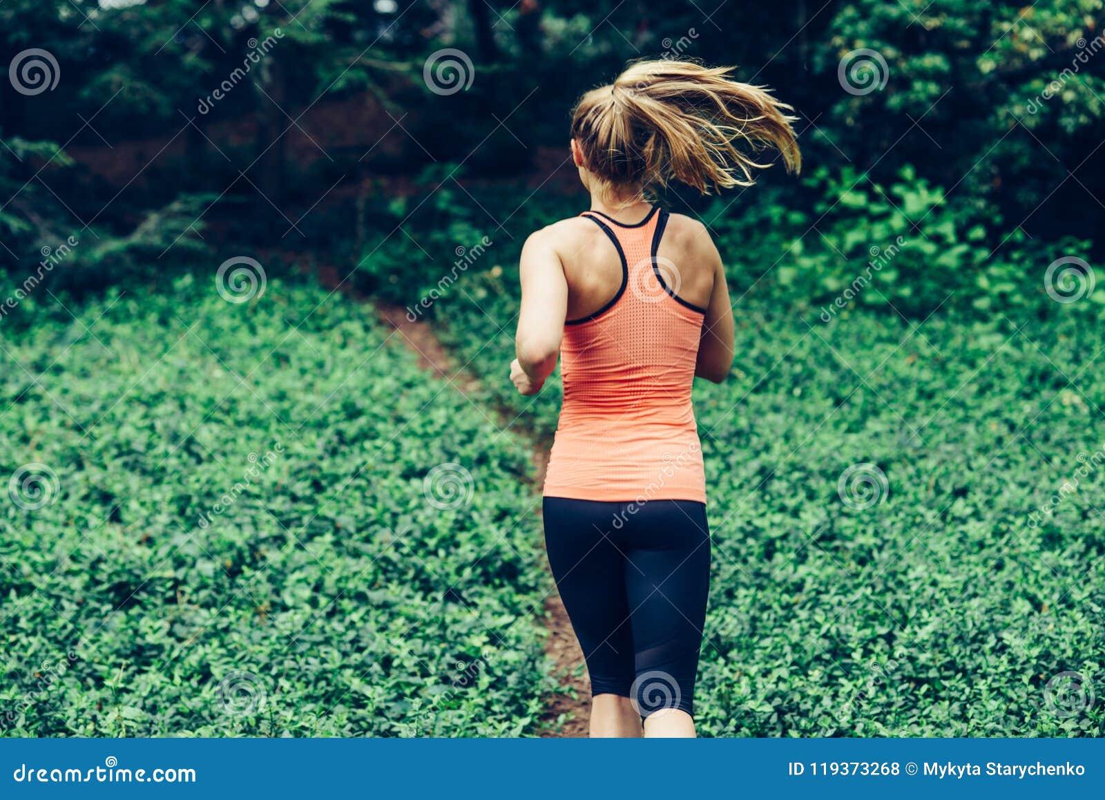 Caucasian kvinnaspring på kläder för sport för skogslinga bärande