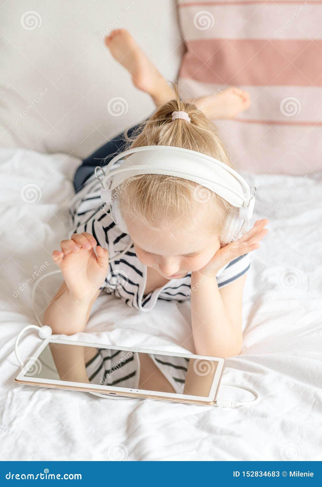 Caucasian liten flicka i hållande ögonen på minnestavla för Headphone i säng