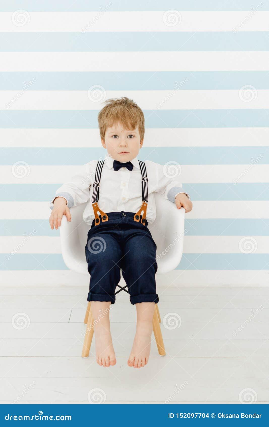 Little boy sitting on toilet in baby toilet seat Stock