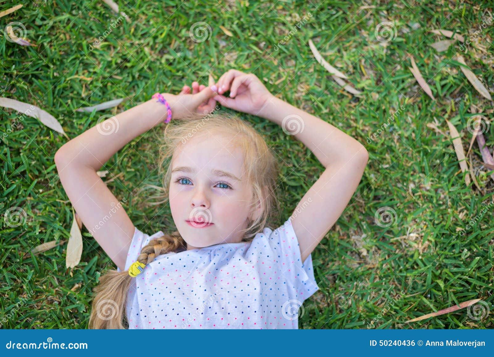 caucasian little girl lay on grass stock photo image