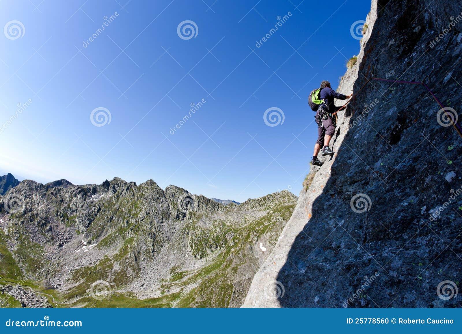 Caucasian male klättrare som klättrar en brant vägg