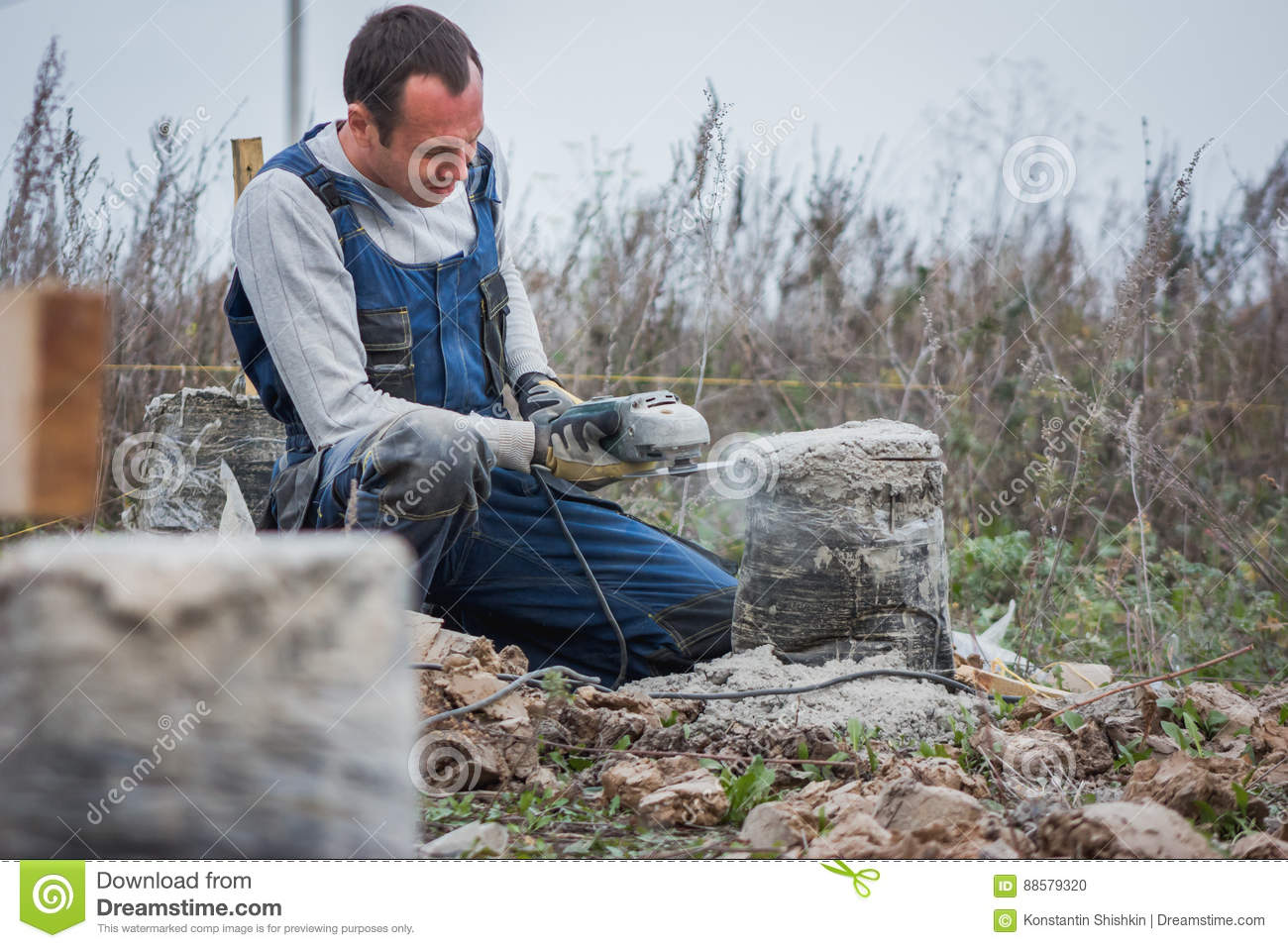 Worker man builder working with circular saw outdoors