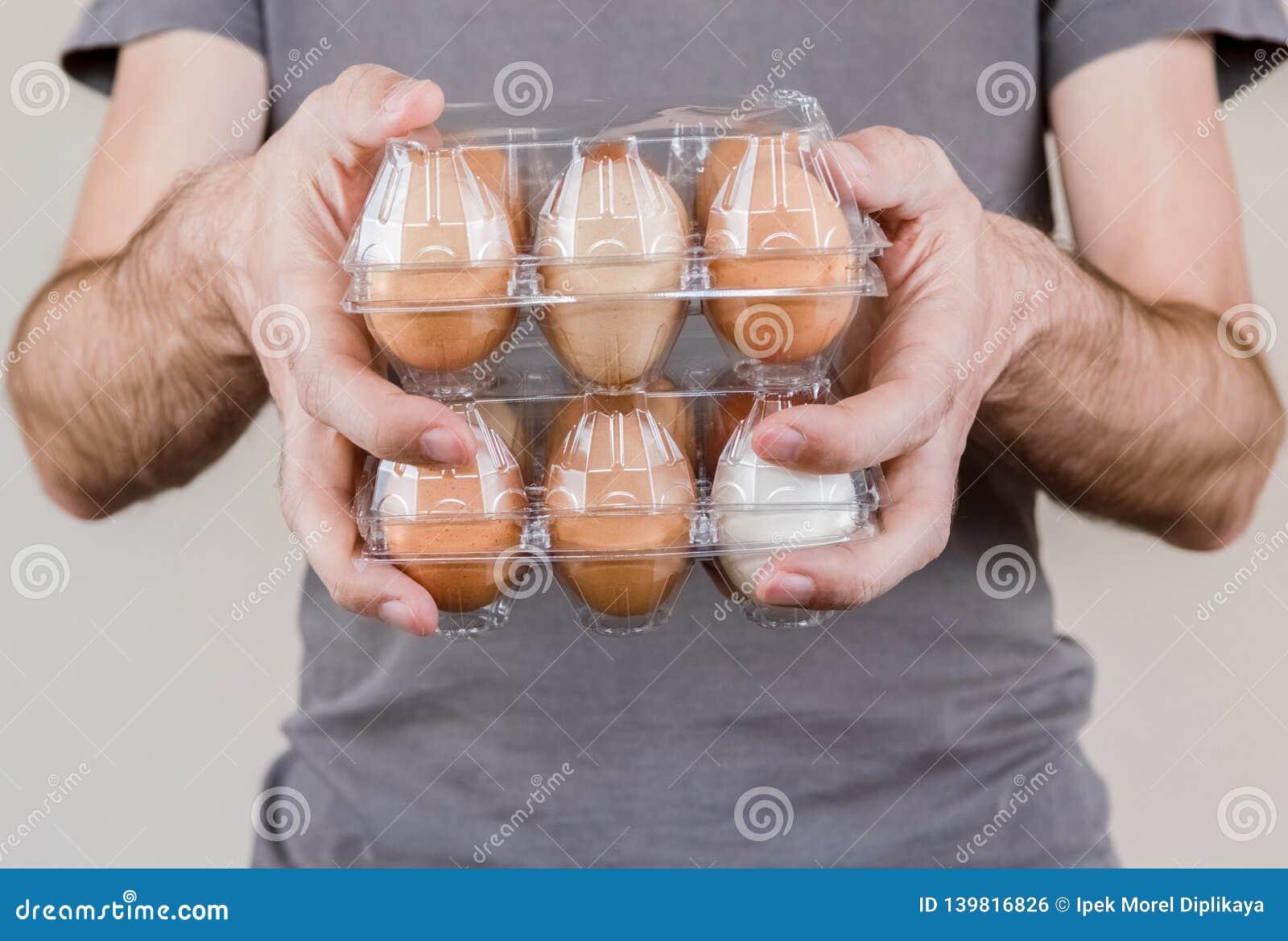 Caucasian man med den gråa tshirten som rymmer två plast- äggaskar fulla av fega ägg
