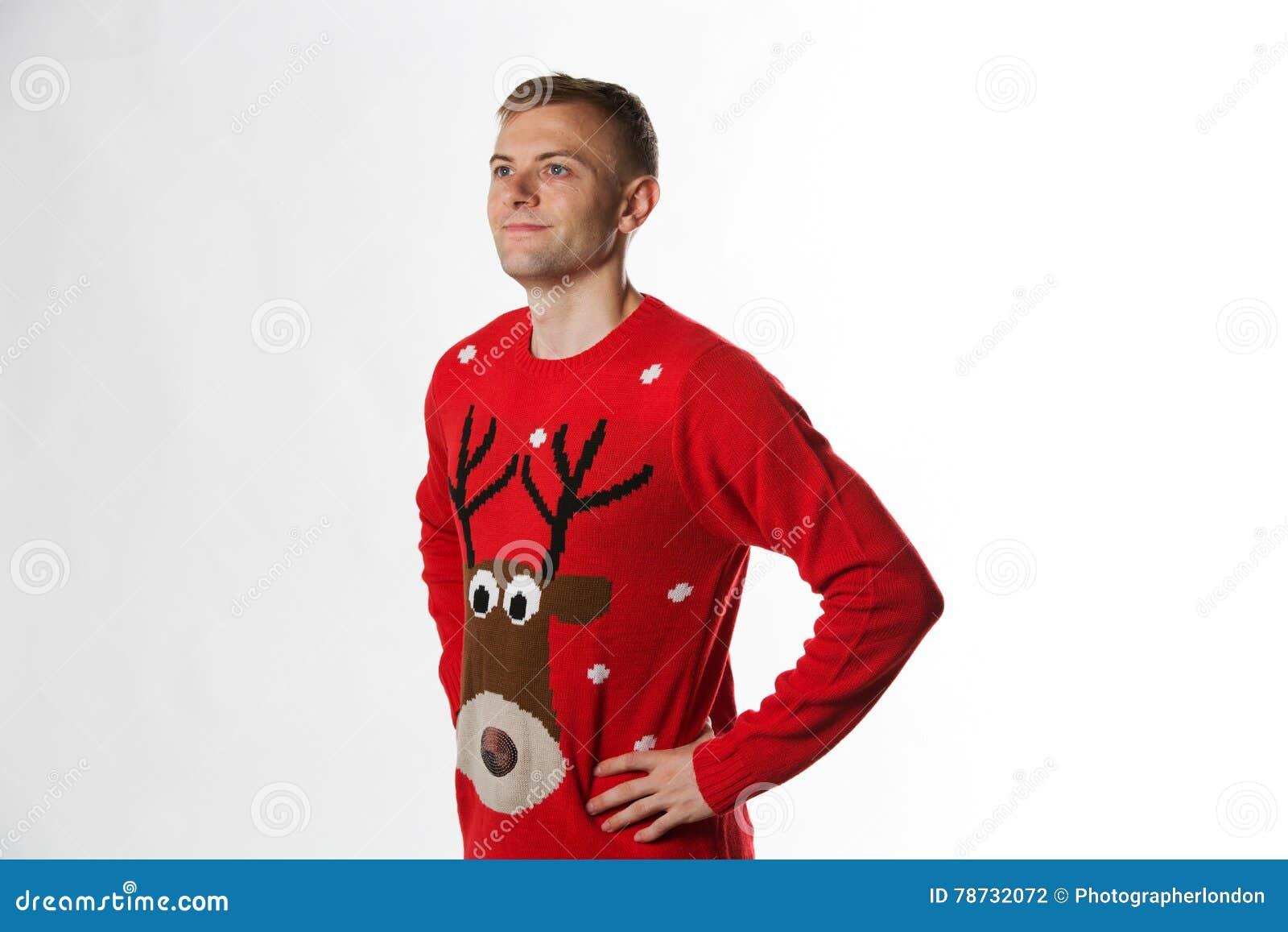 Caucasian man med handen på höftstunden som bär ett julförkläde som ser i väg från kamera