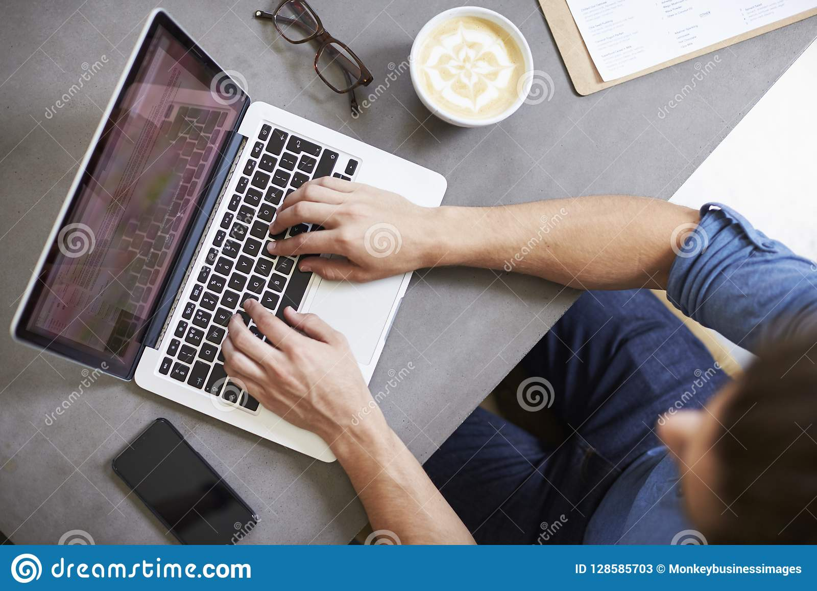 Caucasian man som använder bärbara datorn i en coffee shop, fast utgiftskott