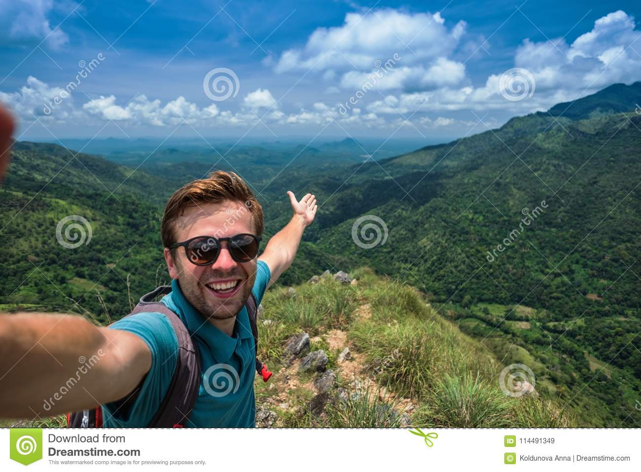 Caucasian man on top of mountain making selfie on background of pretty landscape