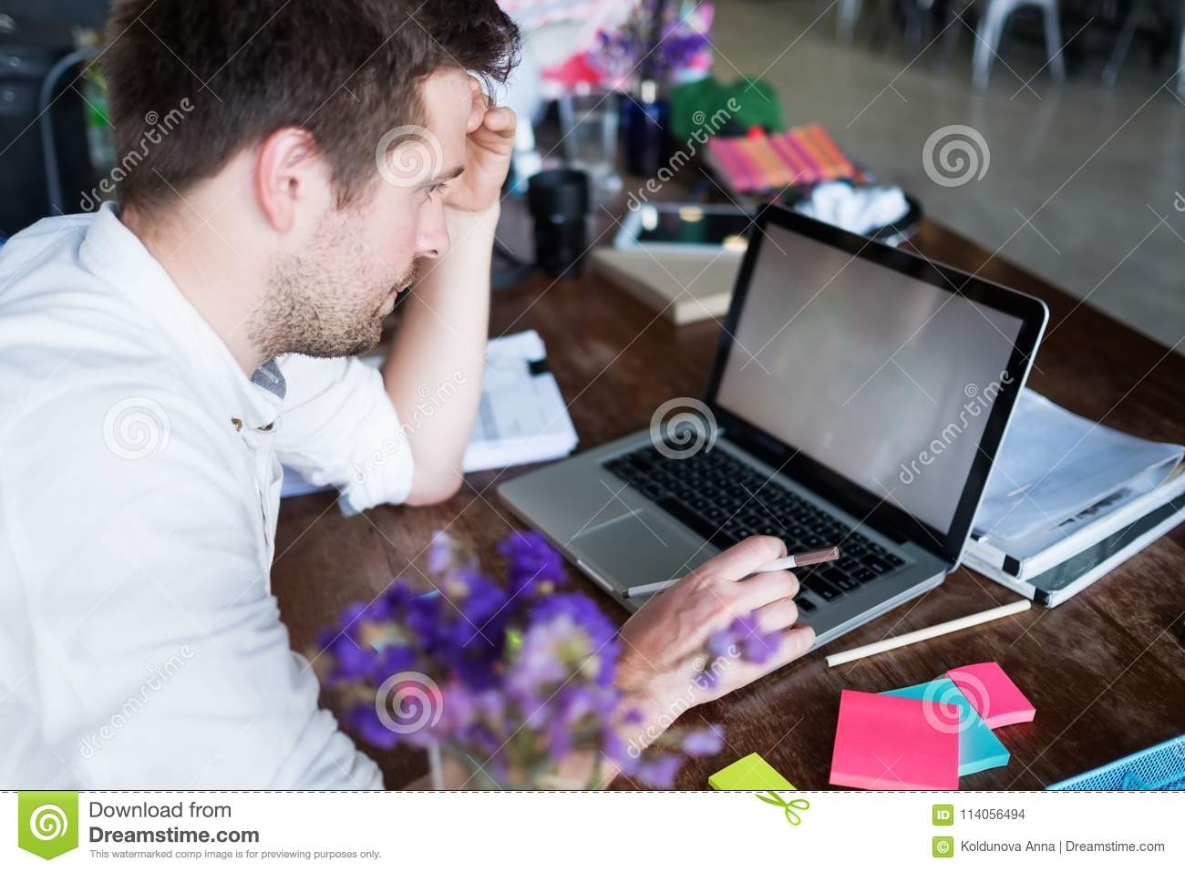 Caucasian man working on laptop while sitting at his modern office place. Concept of young people using coworking place.