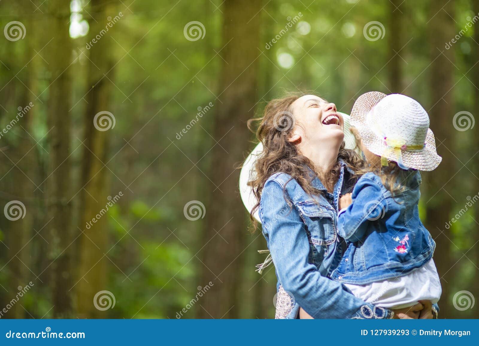 Caucasian moder med hennes lilla dotter som tillsammans poserar i grön sommarskog