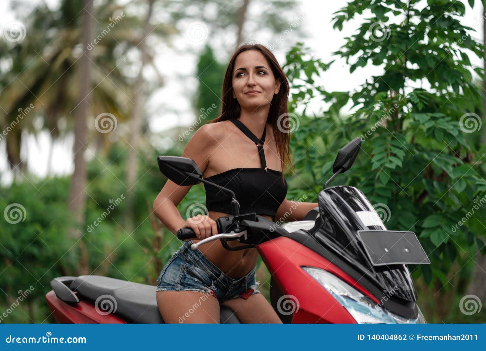 Caucasian nationalitet för brunbränd flicka som kör en röd otorcycle resa på en sparkcykel