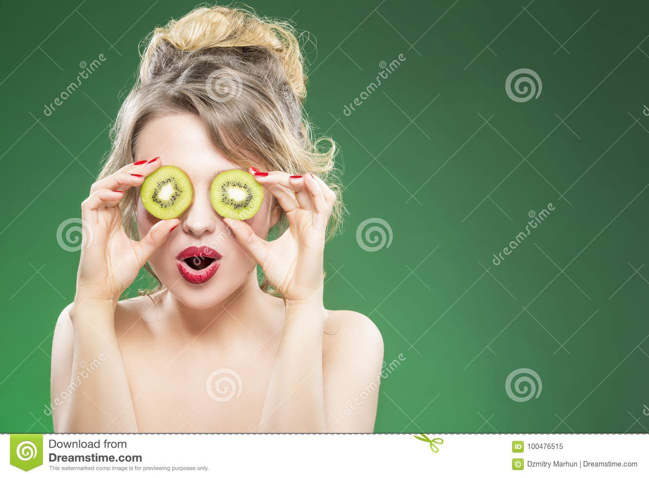Caucasian Nude Model Making Faces while Posing With Two Kiwi Slices