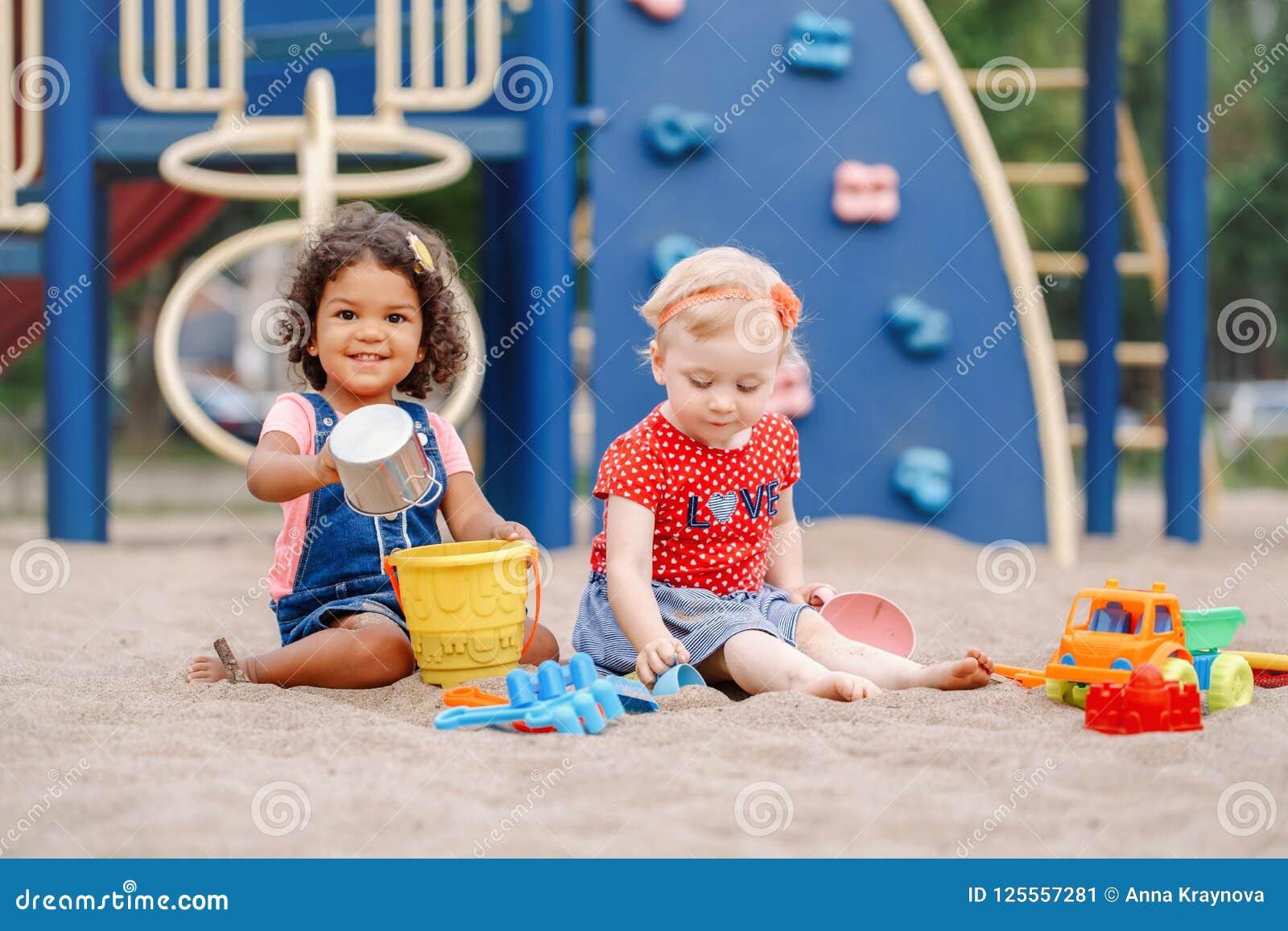 Caucasian och latinamerikansk latin behandla som ett barn barn som sitter, i att spela för sandlåda