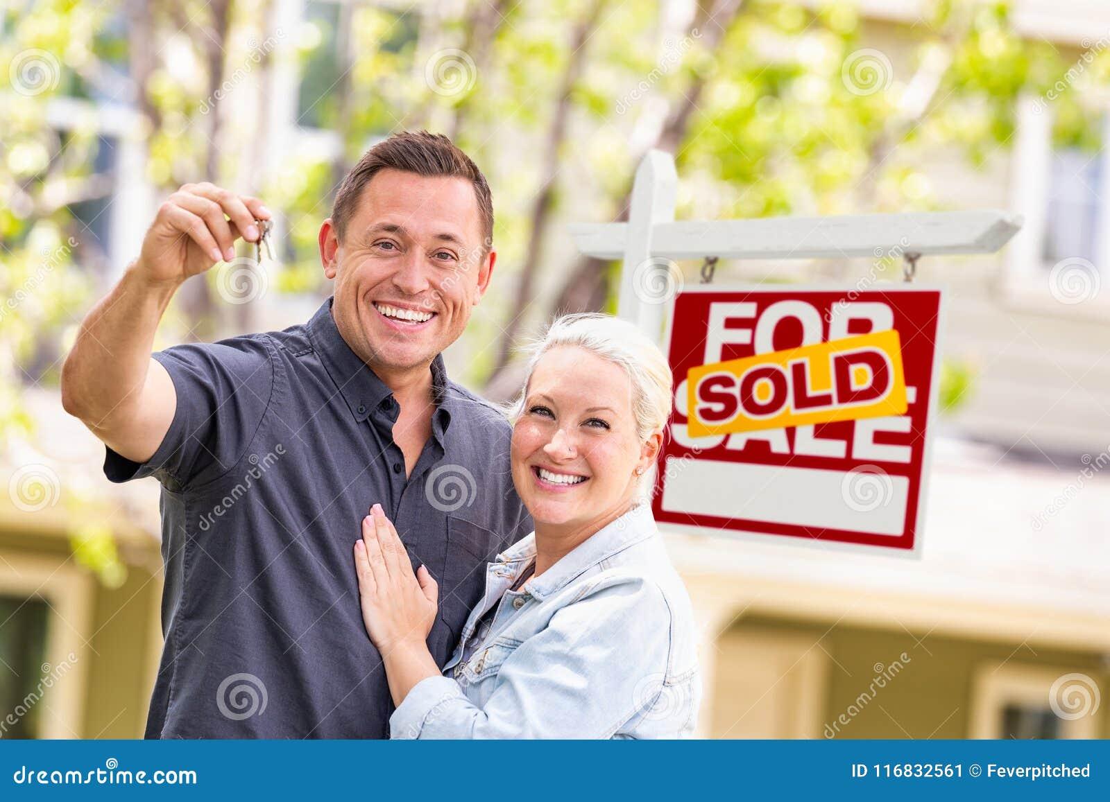 Caucasian par framme av Sold Real Estate tecken- och husintelligens