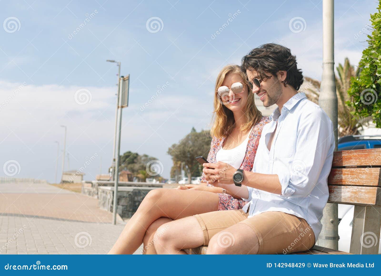 Caucasian par genom att använda mobiltelefonen, medan sitta på bänk på en solig dag