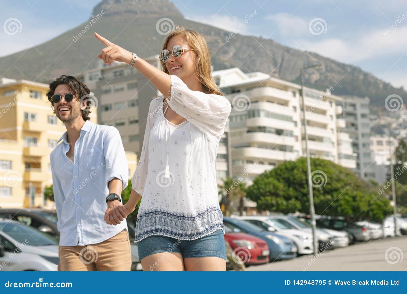 Caucasian par som går på promenaden på en solig dag