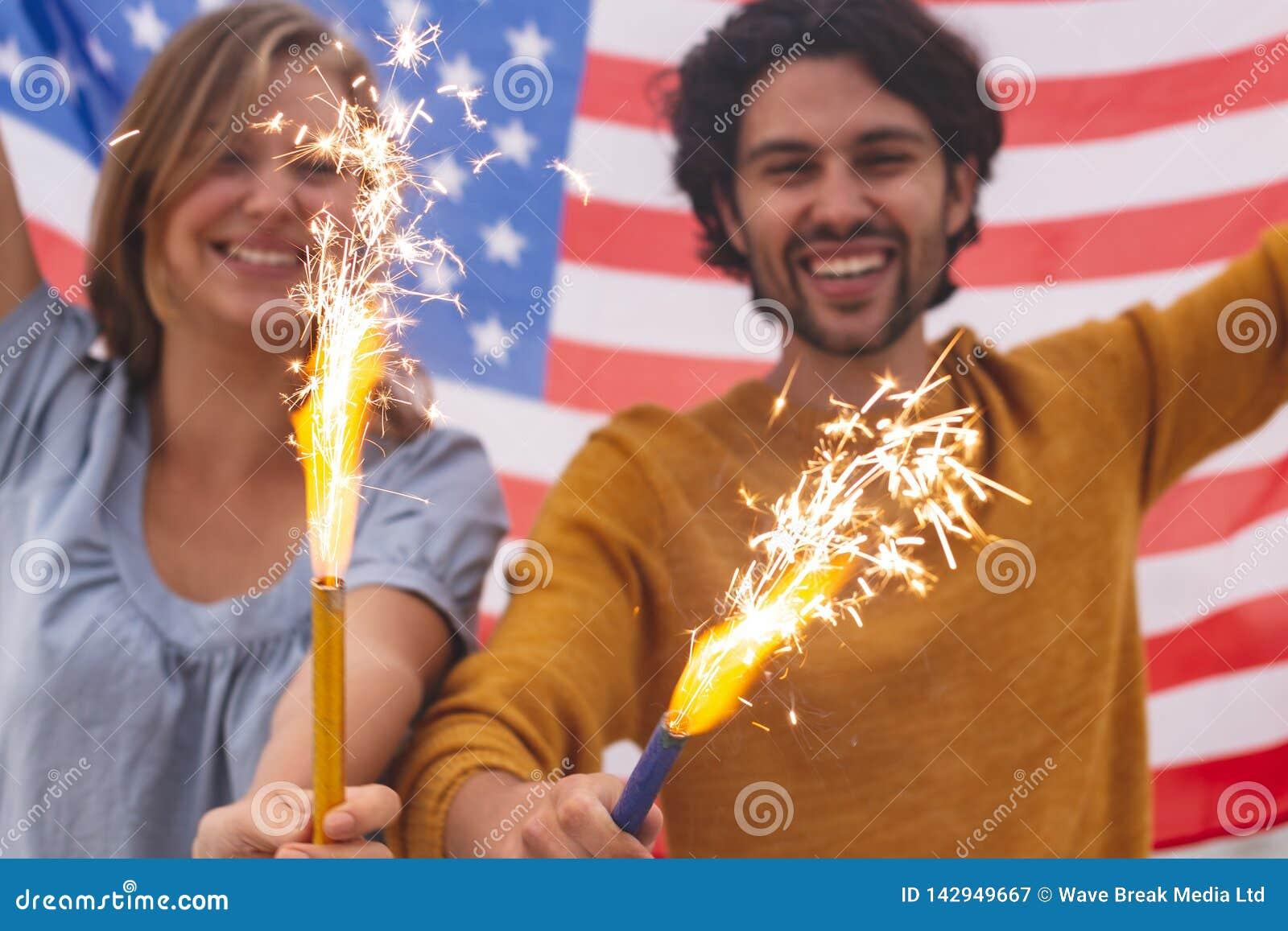 Caucasian par som spelar med brandsmällaren, medan rymma amerikanska flaggan
