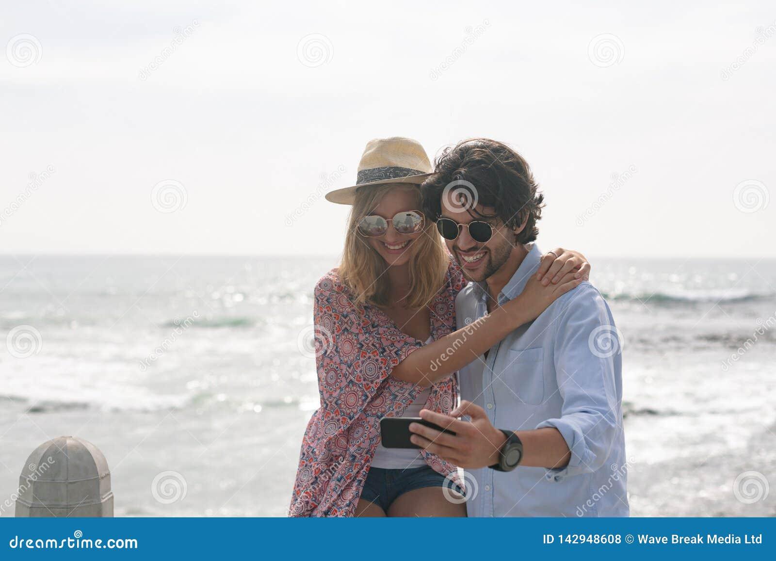 Caucasian par som tar selfie, medan sitta nära havssida på promenad