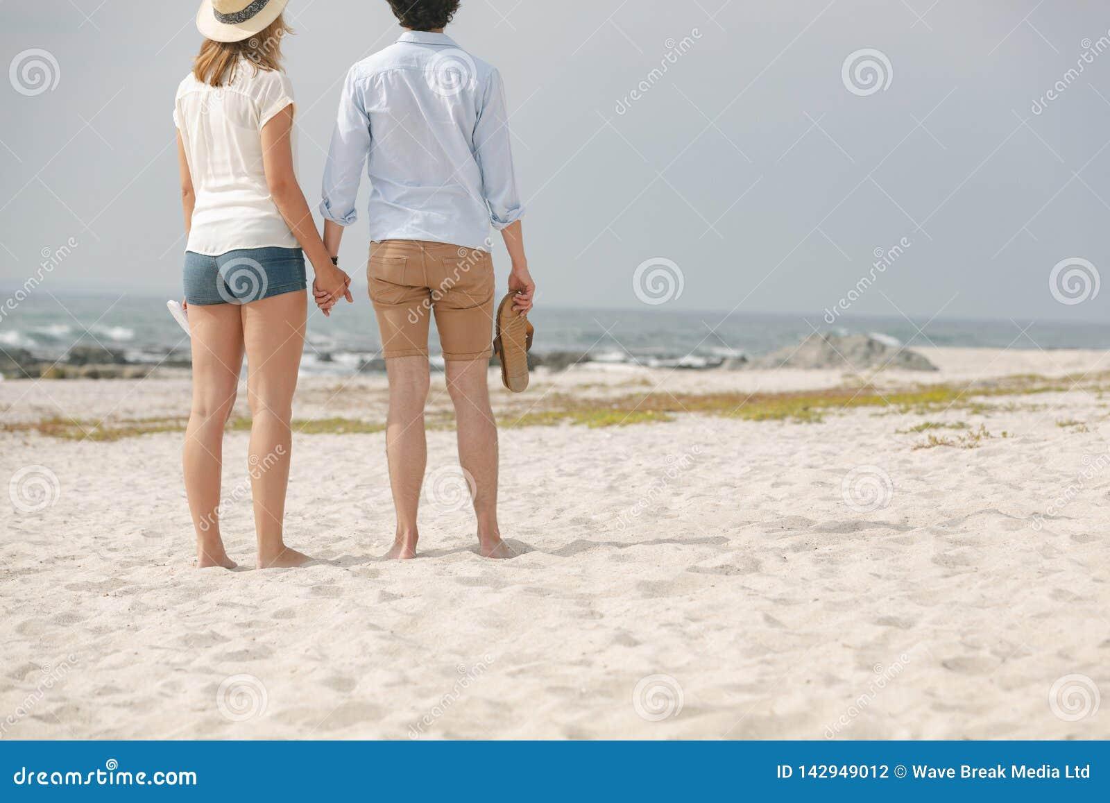Caucasian paranseende på stranden med skodon i hand