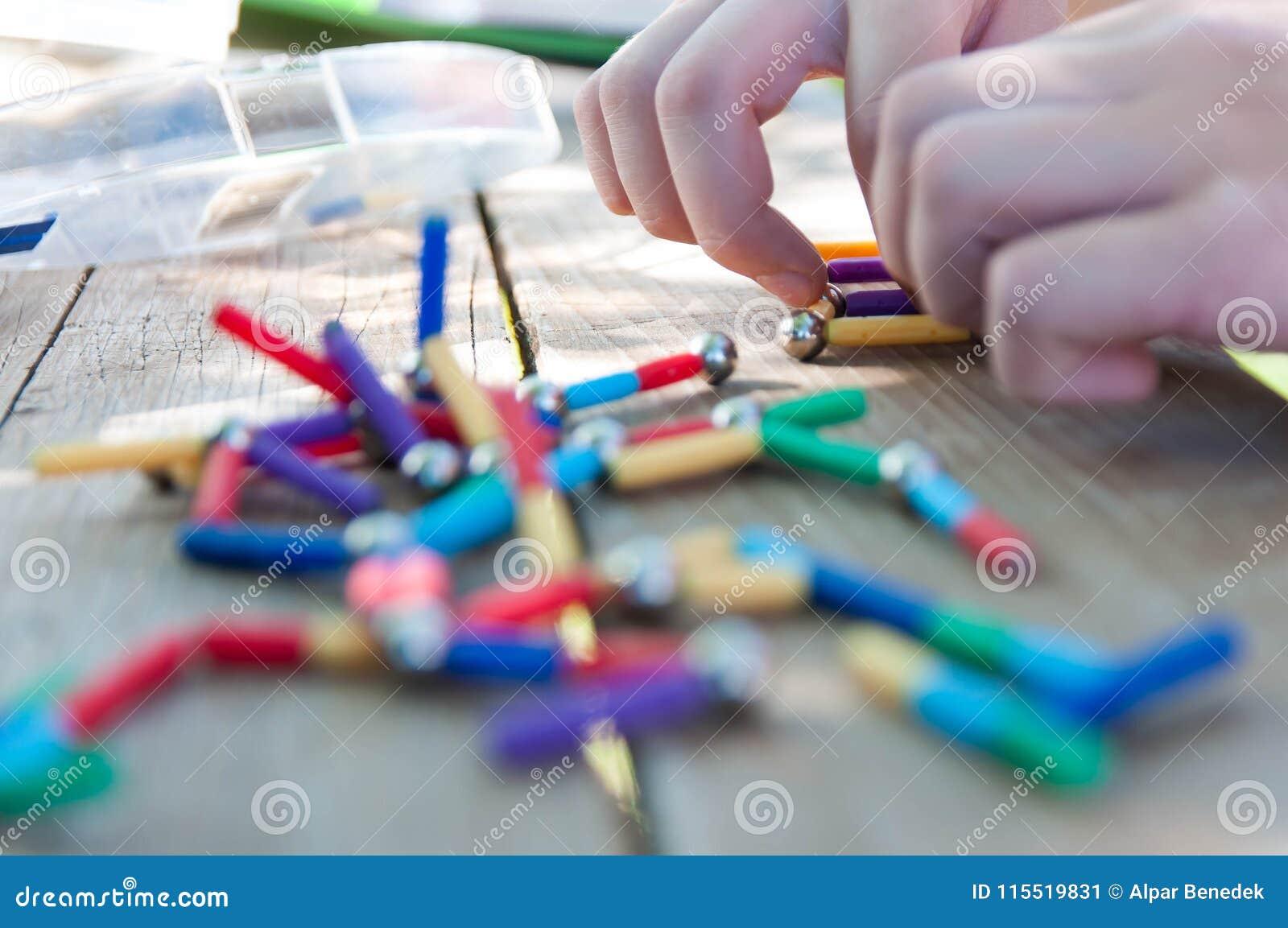 Caucasian pojke som spelar med magnetiska leksaker