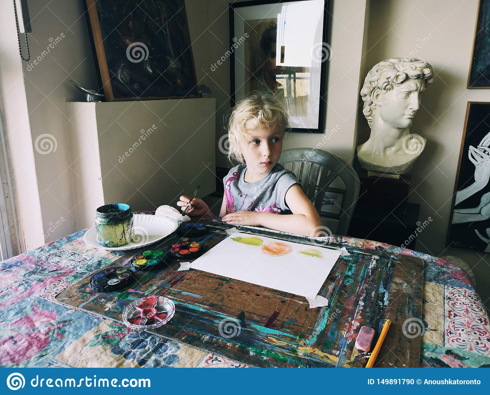 Caucasian preschooler girl sitting in art studio concentrated on painting fruits with brushes and water color paints