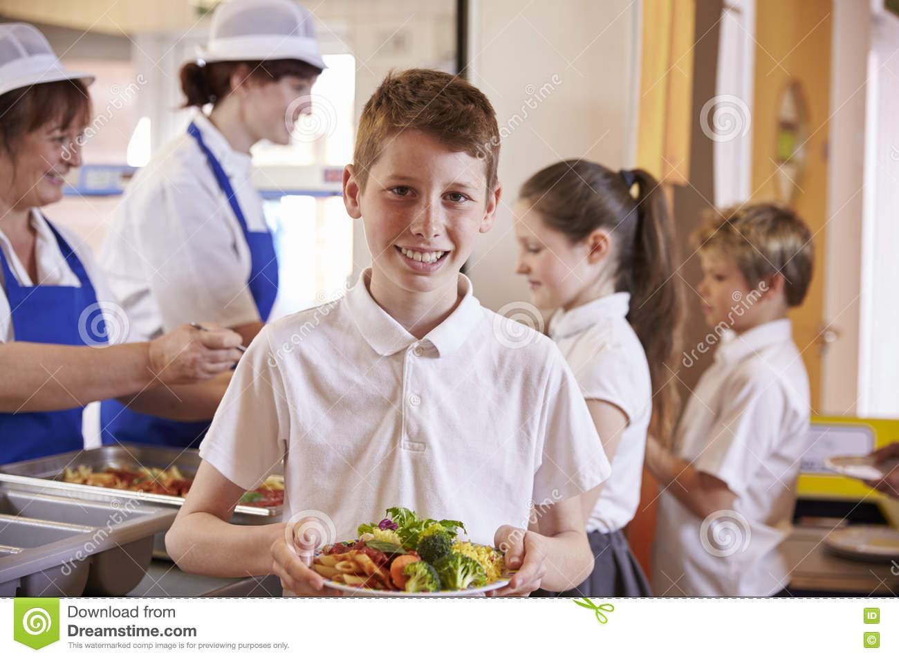 Caucasian schoolboy holds plate of food in school cafeteria