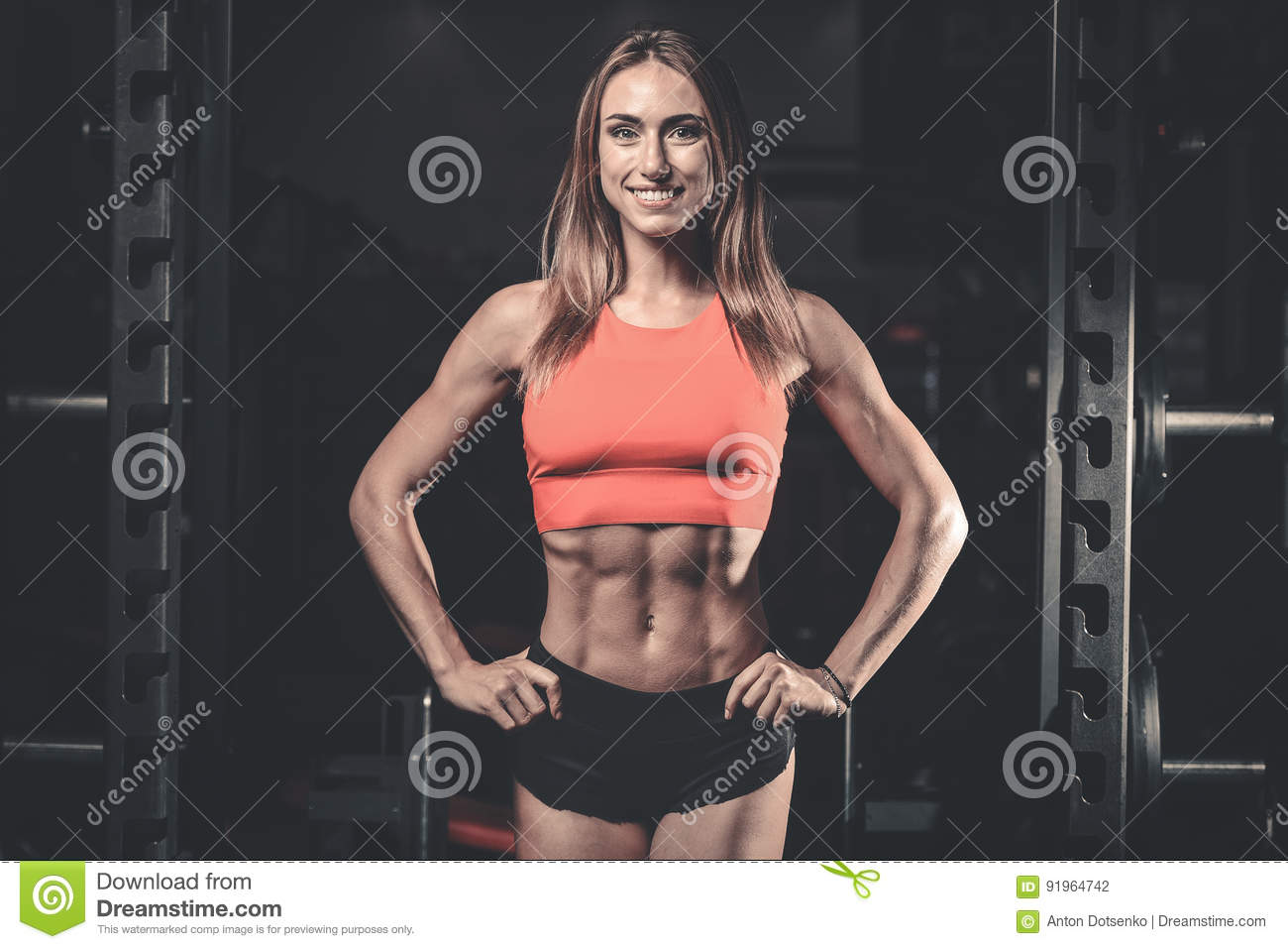 Caucasian fitness female model in gym close up abs