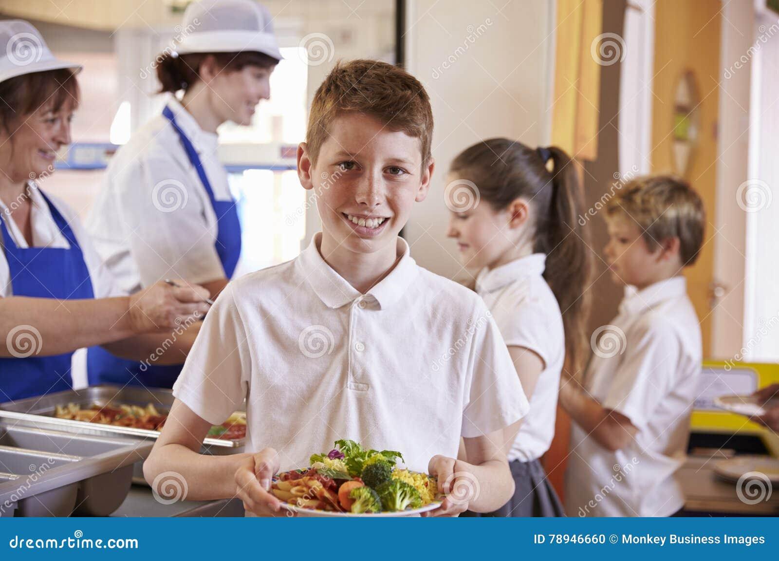 Caucasian skolpojkehållplatta av mat i skolakafeteria