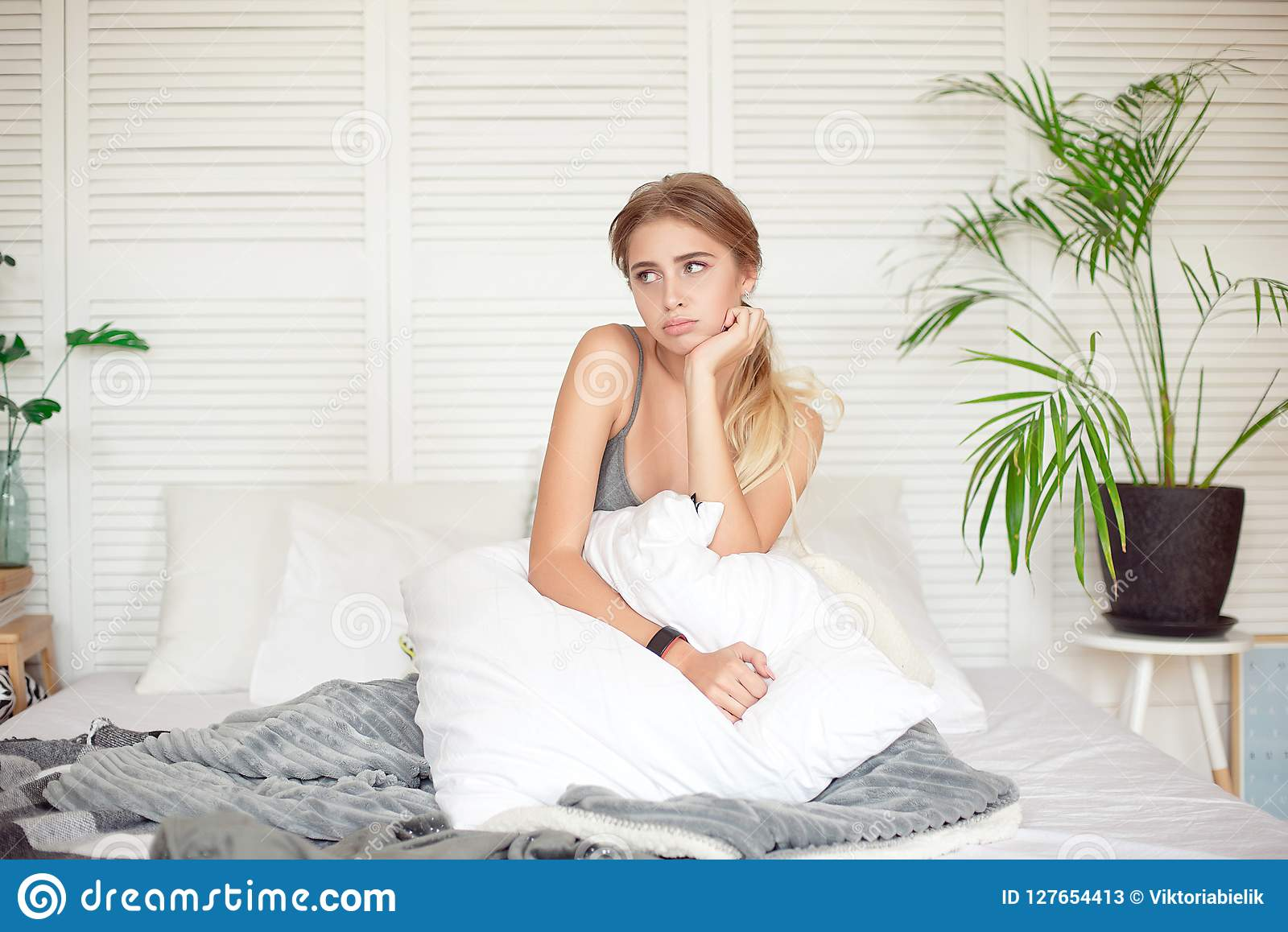 Caucasian sleepy young attractive woman feeling drowsy after woke up, sits on the bed having bad mood after sleepless