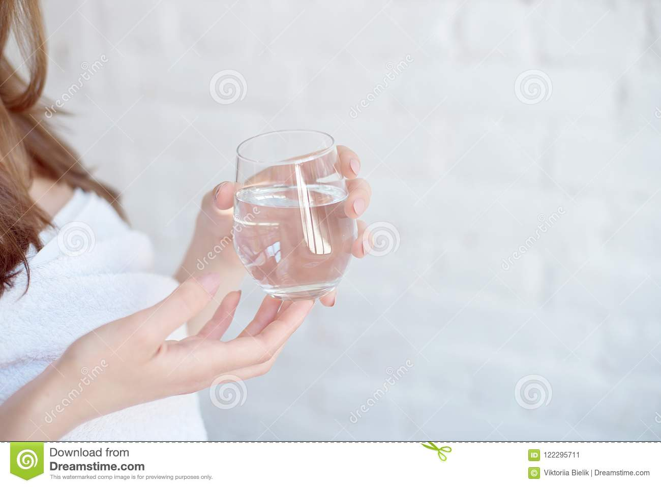 Caucasian smiling woman after spa covered with white towel holding a glass of water