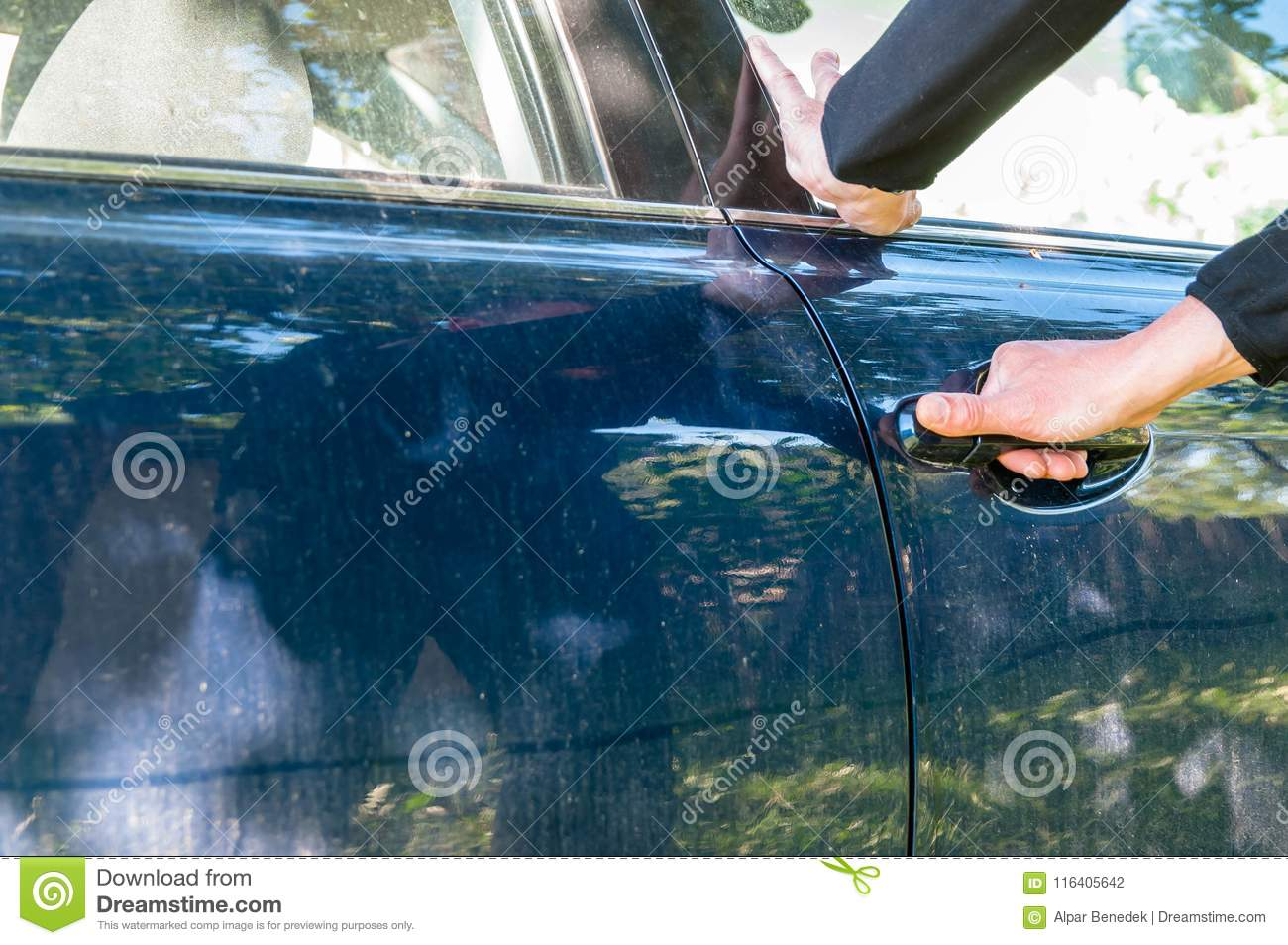 Caucasian thief hand trying to open a car door