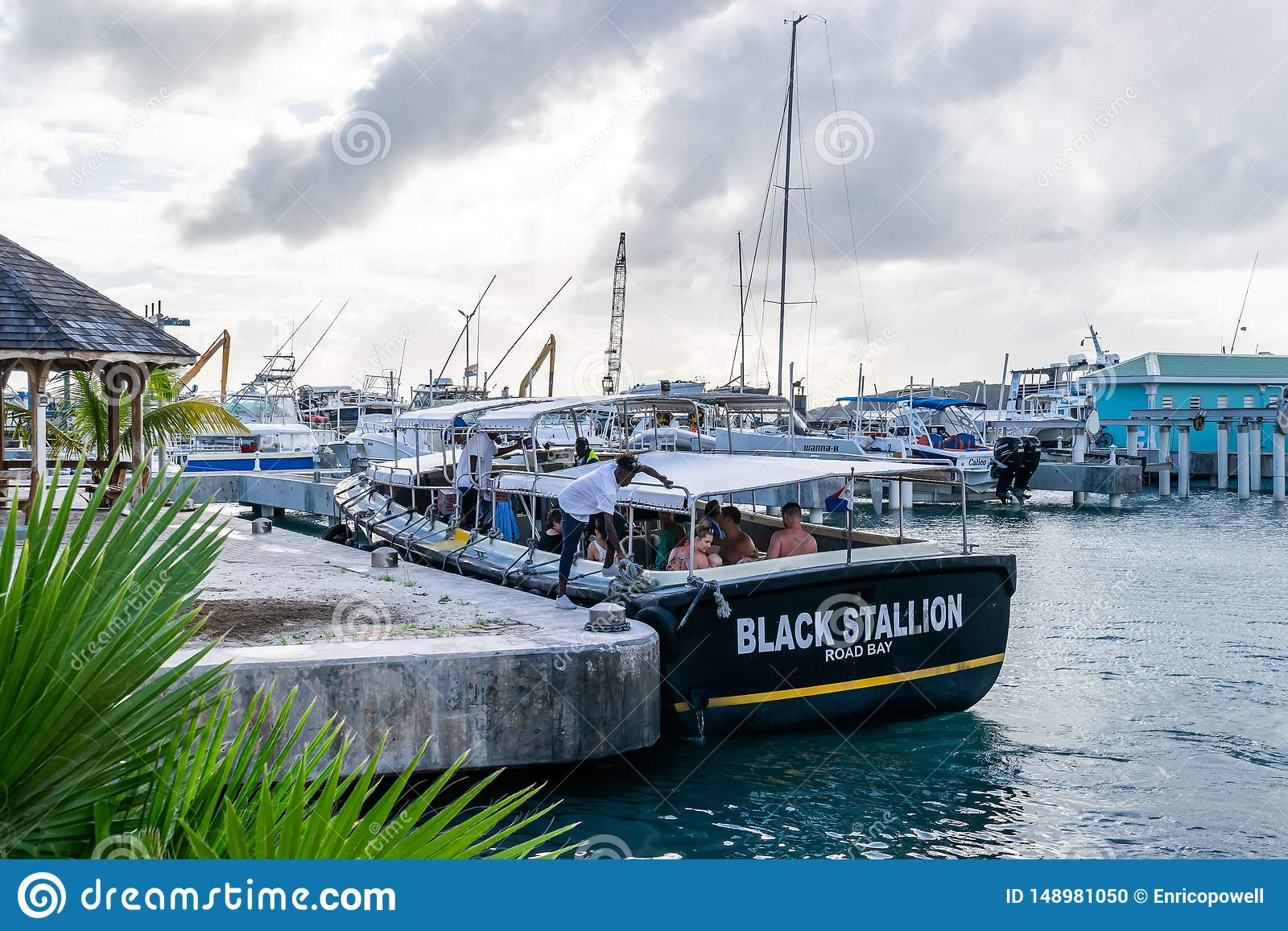 Caucasian tourists on Black Stallion Road Bay tour boat in boatyard Crew unties ropes from marine bollards for sailing