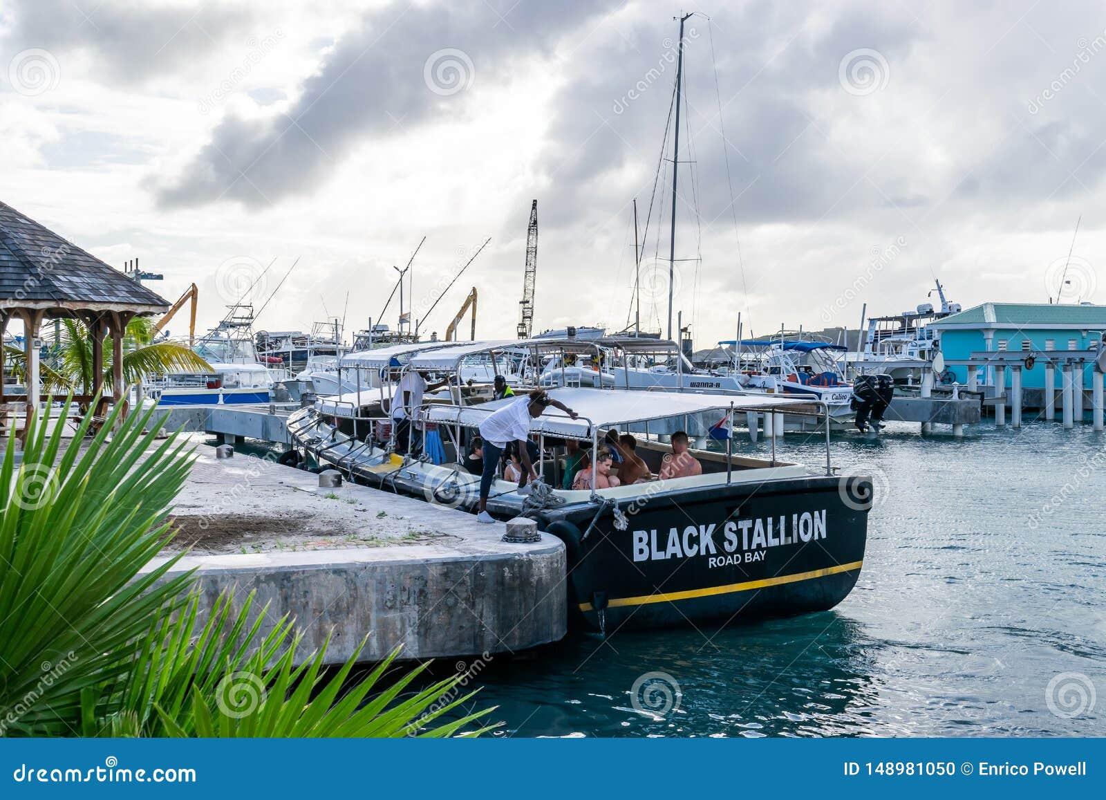 Caucasian turister på svart hingst väg somfjärden turnerar fartyget i boatyardbesättning, knyter upp rep från marin- pollare för