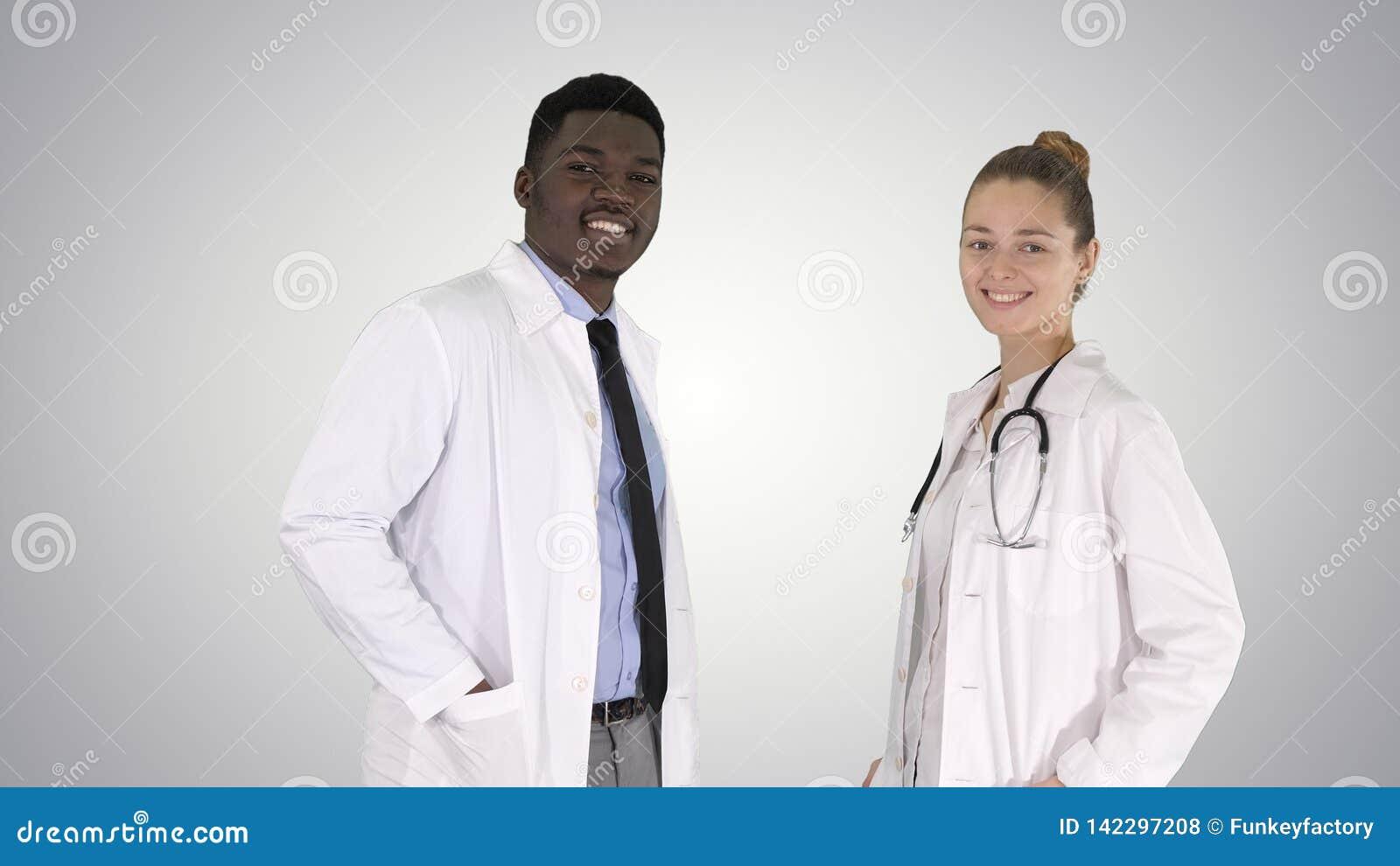 Caucasian två och afro- amerikanskt le doktorsanseende som in ser till kameran på lutningbakgrund