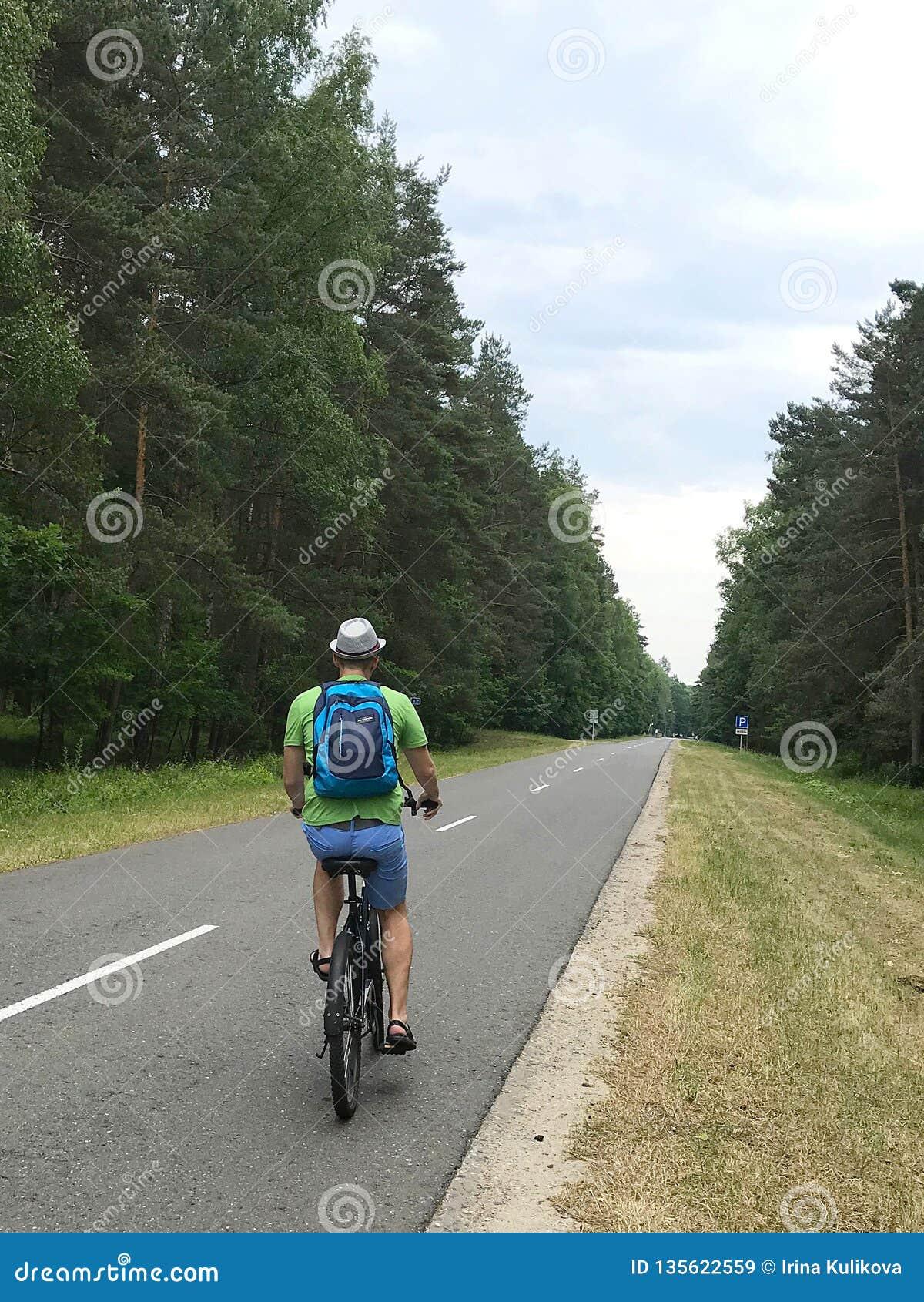 Caucasian ung man med ryggsäcken som rider en cykel på en asfaltväg som omges av skogbaksidasikt