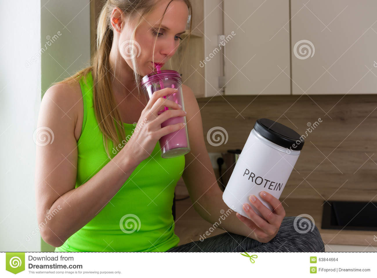 Caucasian woman in gym suit drinking protein shake in the kitchen