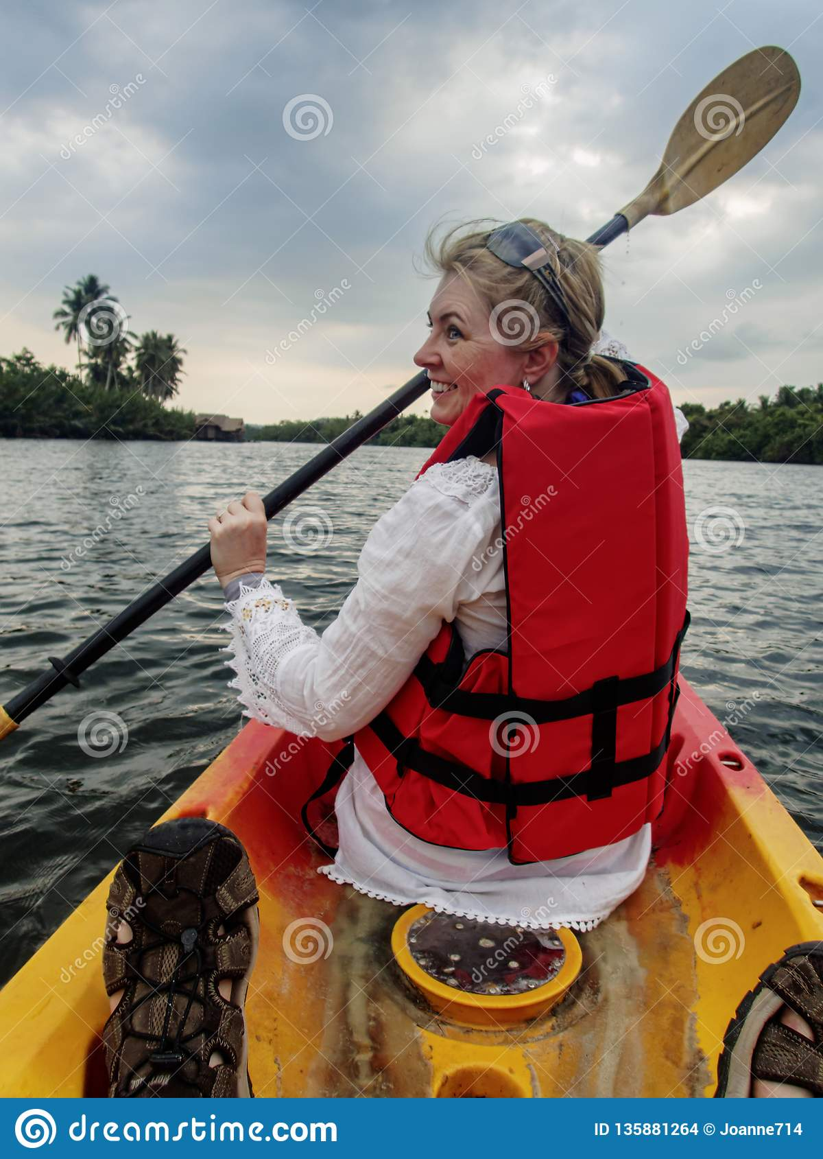 Caucasian woman, mod 40`s kayaking through the cambodian Jungle on the River Kong, wearing red life vest