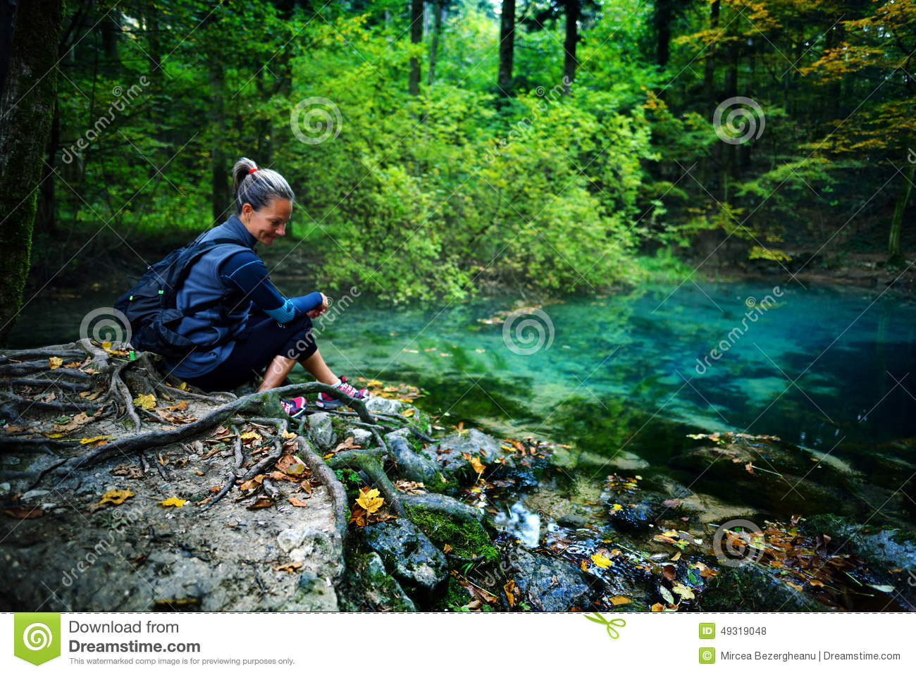 caucasian woman tourist relaxing by the river, in the forest, Ochiul Beiului, Romania