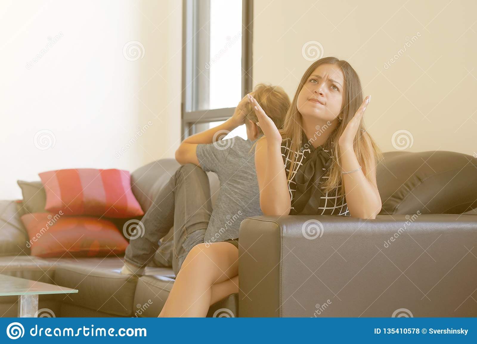 Sad couple after argument or breakup sitting on a sofa in the living room in a house indoor