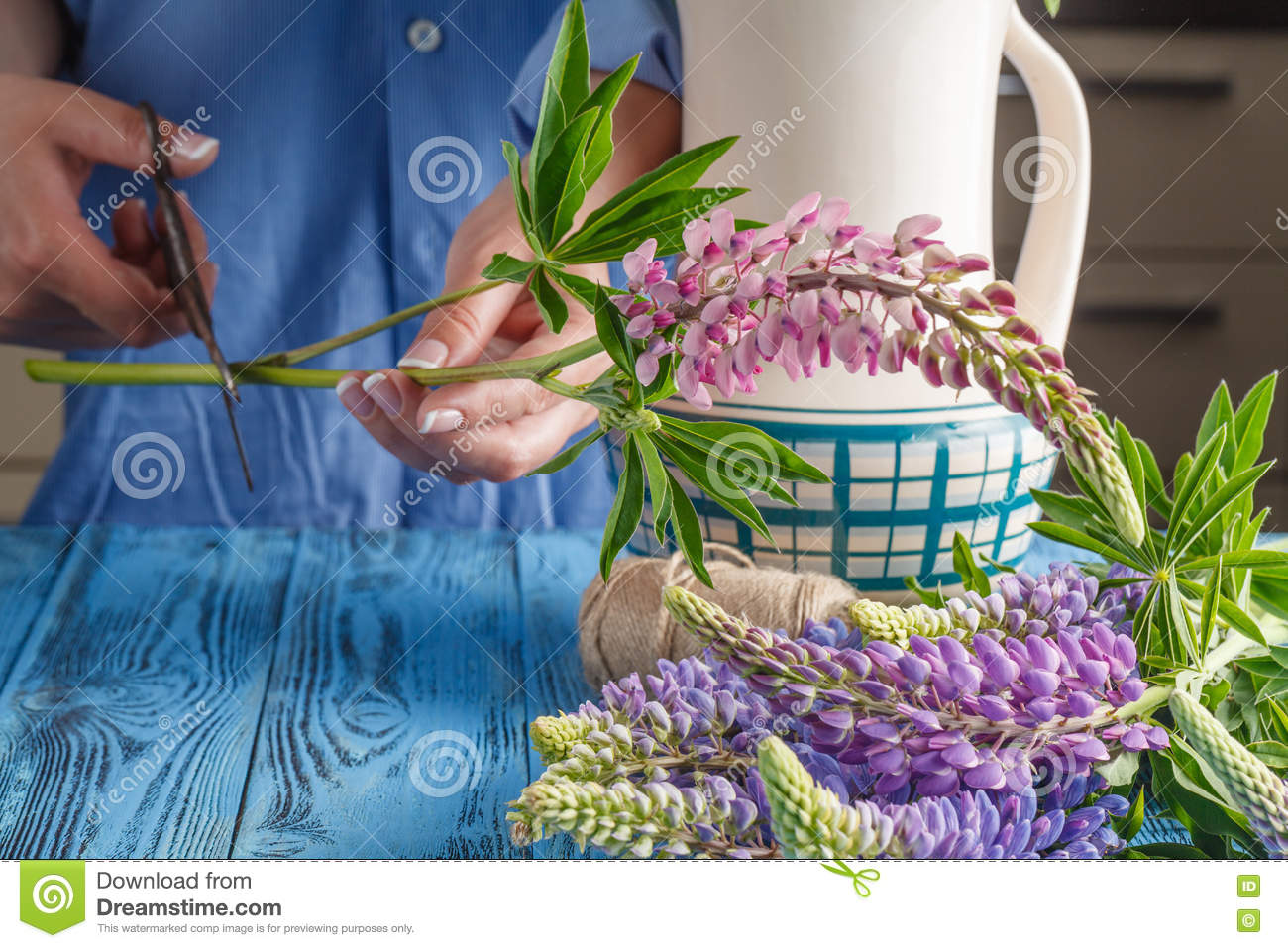 Caucasian Young Woman Arranging Flowers In Vase In Kitchen Stock ...