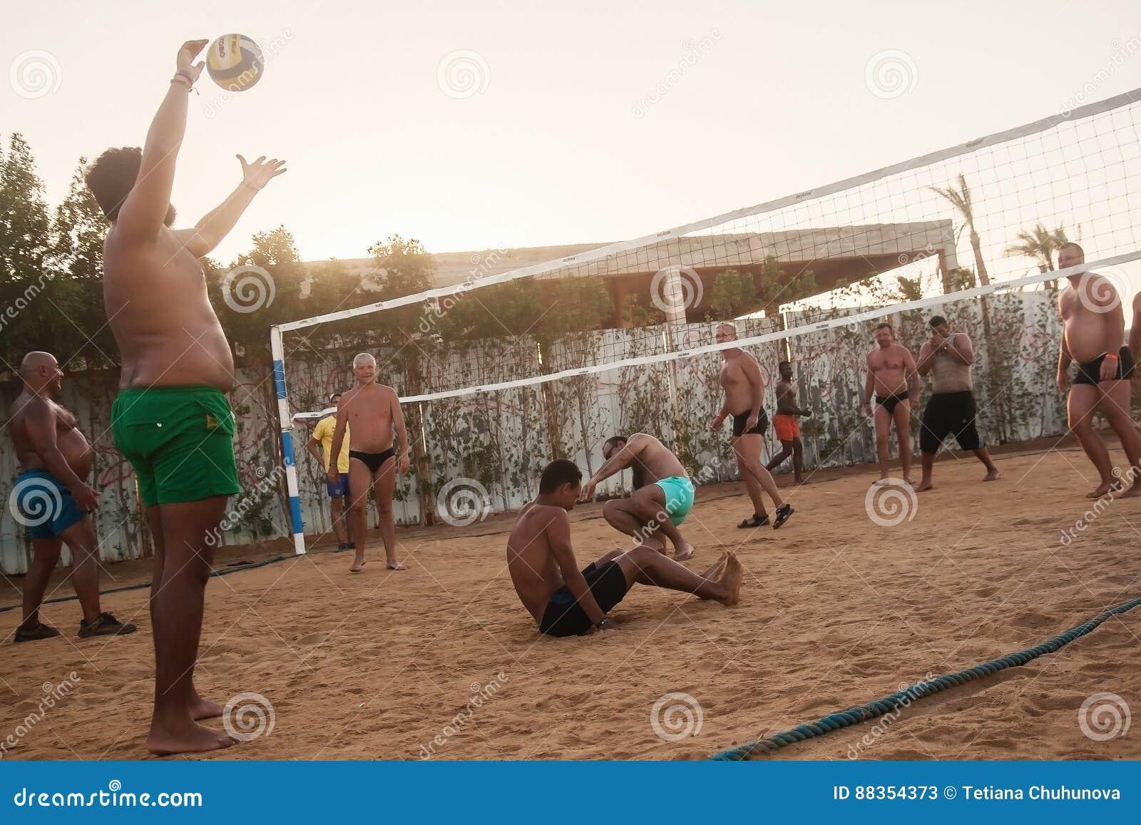 Caucasians masculinos, árabes, africanos que jogam o voleibol na praia