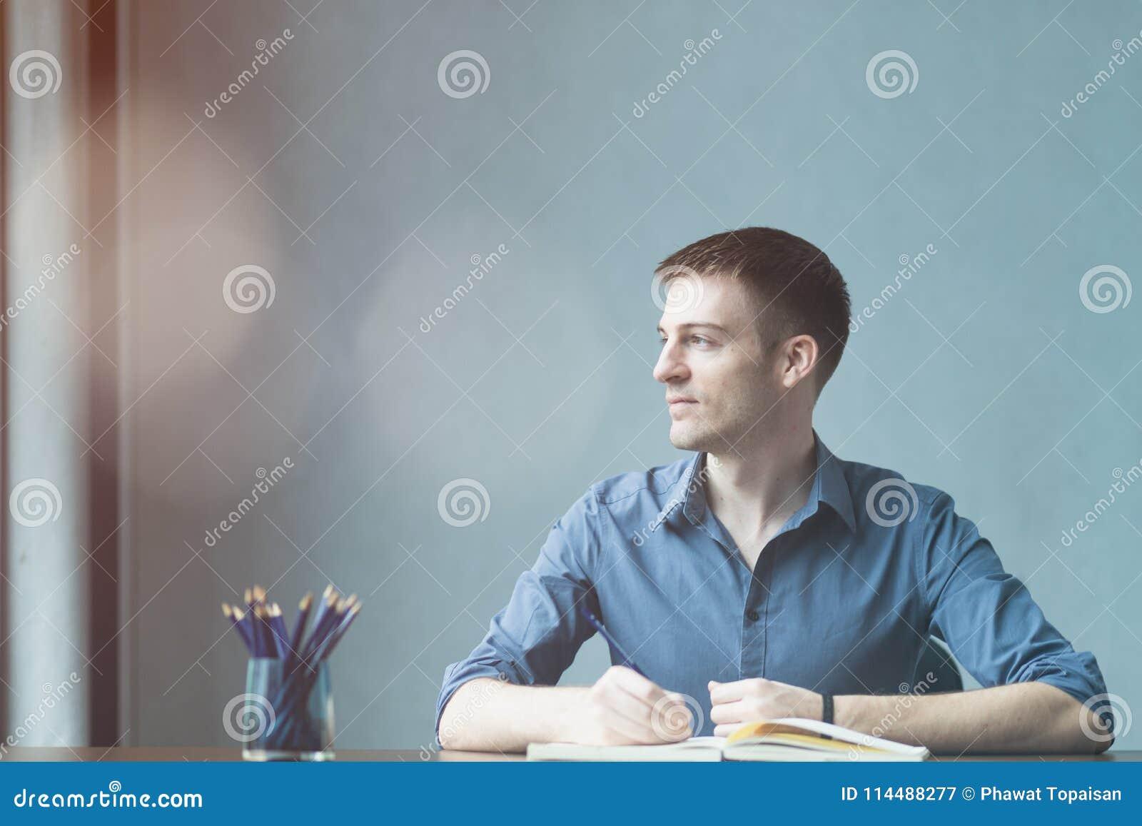 Caucasians novos do homem de negócios que sentam-se na tabela do escritório da mesa e que tomam notas no caderno Escrevendo e olh