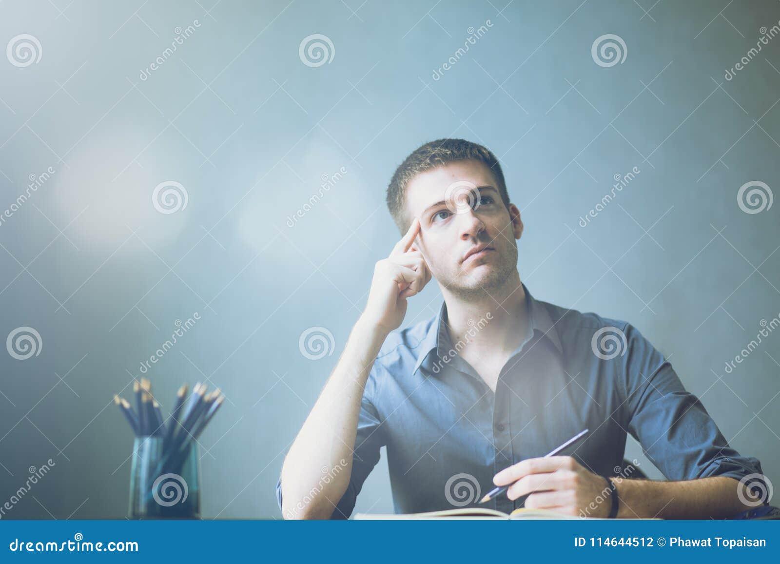 Caucasians novos do homem de negócios que sentam-se na tabela do escritório da mesa e que tomam notas no caderno Escrita e vista